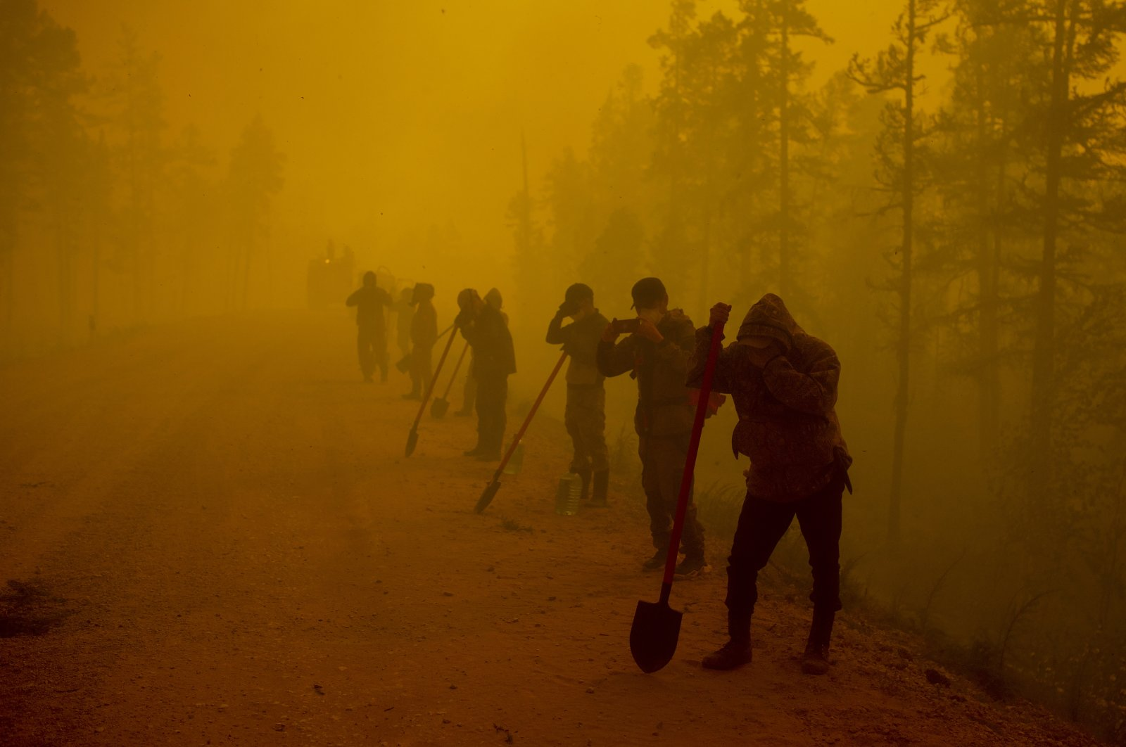 Volunteers pause while working at the scene of forest fire near Kyuyorelyakh village at Gorny Ulus area west of Yakutsk, Russia, Aug. 7, 2021. (AP Photo)