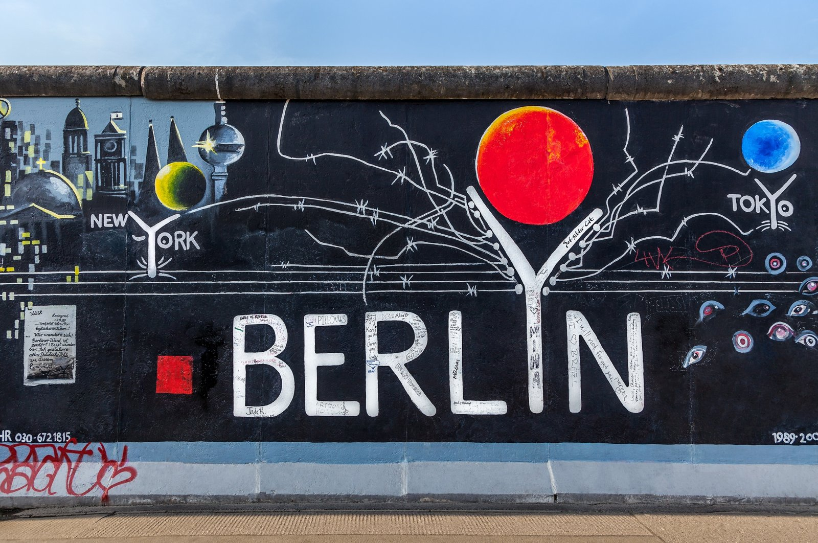 Various graffiti marking different cities can be seen on a part of the original Berlin Wall at East Side Gallery, Berlin, Germany, Sept. 15, 2014.(Shutterstock Photo)