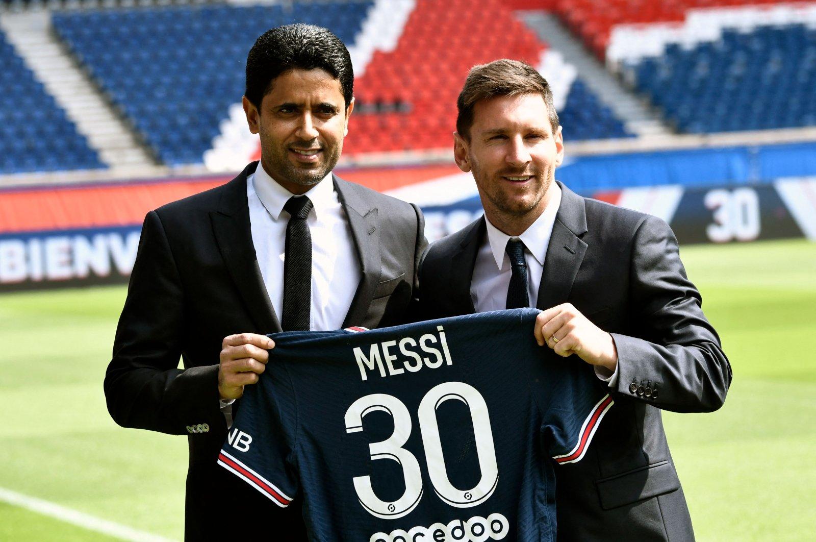Lionel Messi (R) poses with Paris Saint-Germain President Nasser Al-Khelaifi (L) as he holds up his number 30 shirt during a press conference at Parc des Princes, Paris, France, Aug. 11, 2021. (AFP Photo)