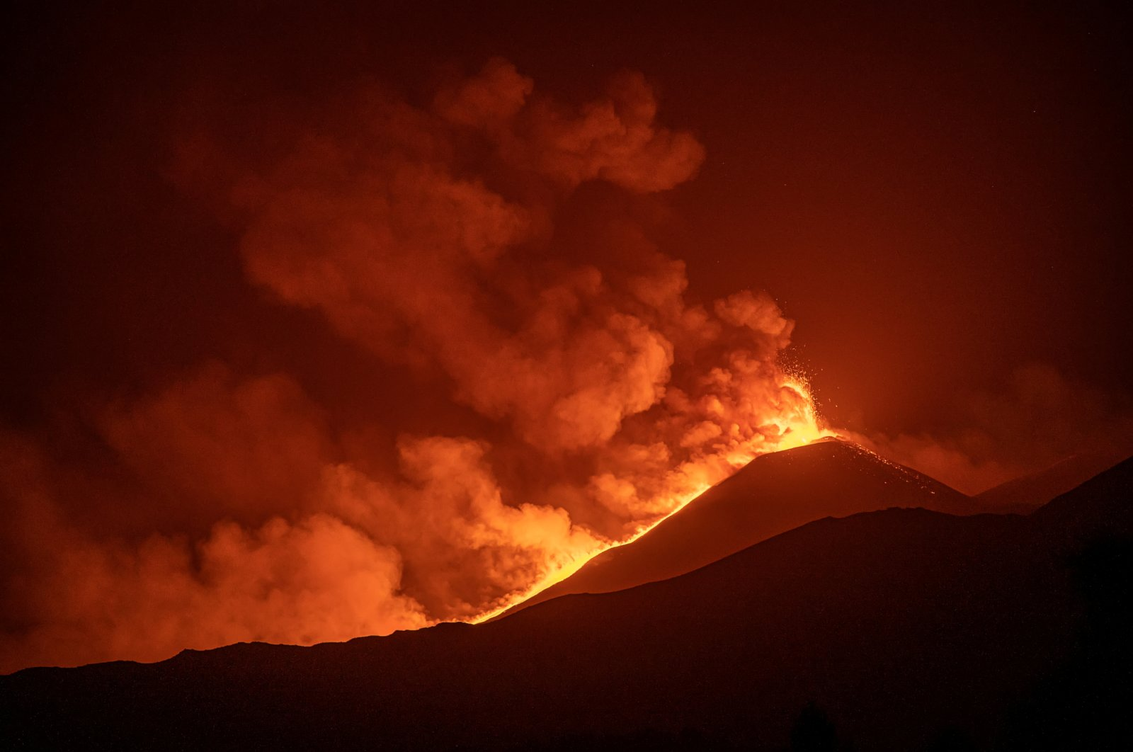 Streams of red hot lava flow as Mount Etna, Europe's most active volcano, erupts as seen from Rifugio Citelli, Italy, Aug. 9, 2021. (Etna Walk/Marco Restivo/Handout via Reuters)