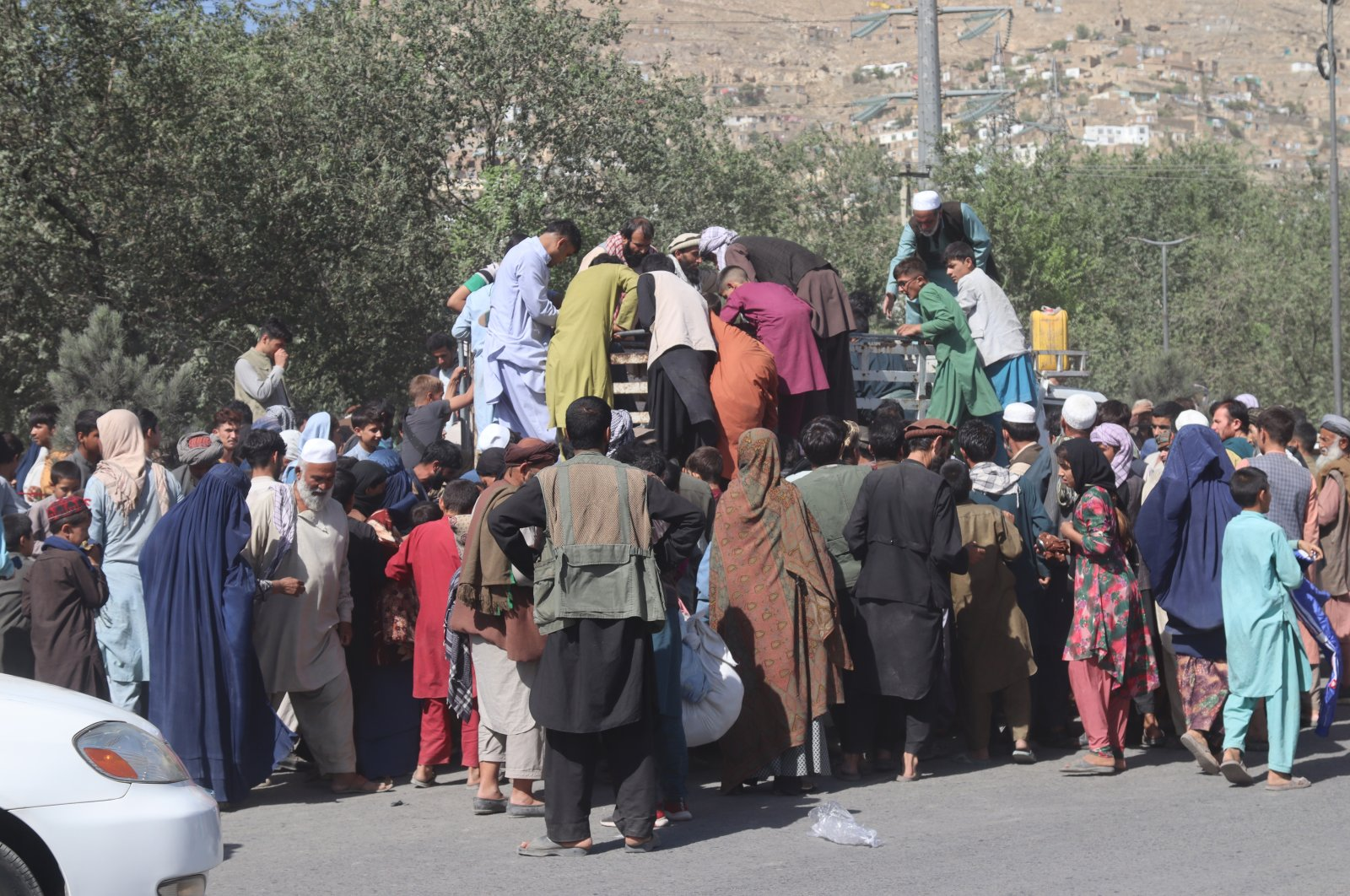 Afghans who are displaced from Kunduz and Takhar provinces due to fighting between Taliban and Afghan forces gather to collect food, as they live in temporary shelters at a camp in Kabul, Afghanistan, Aug. 10, 2021. (EPA-EFE Photo)