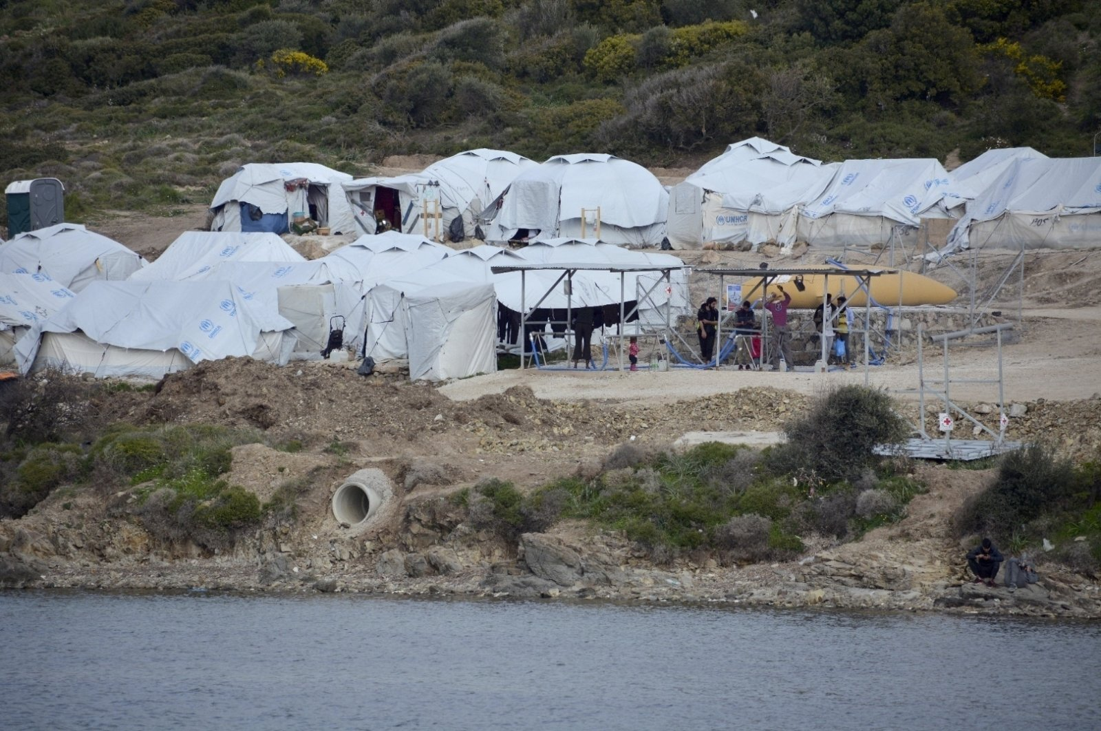 Migrants gather outside their tents in a refugee camp, on the eastern Aegean island of Lesbos, Greece, March 29, 2021. (AP Photo)