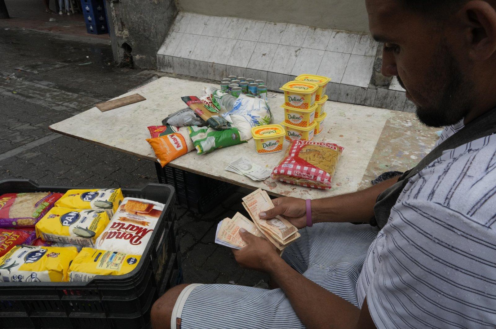 A street vender counts his money in Caracas, Venezuela, Aug. 5, 2021. (AP Photo)
