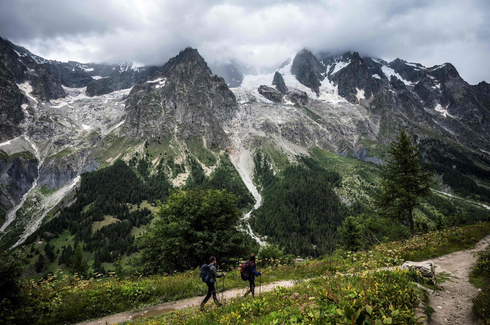 Hikers walk on a path near the Planpicieux (C) and Grand Jorasses Glaciers (R) in Courmayeur, Alps Region, north-western Italy, Aug. 3, 2021. (AFP Photo)