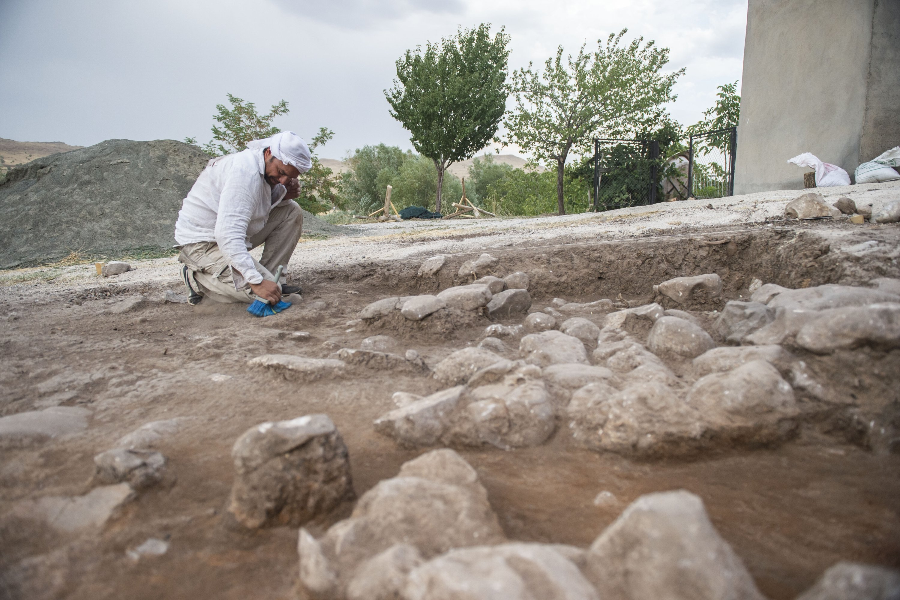 An archaeologist works during excavations at the Tozkoparan Mound site in Tunceli, Turkey, Aug. 11, 2021. (AA Photo)
