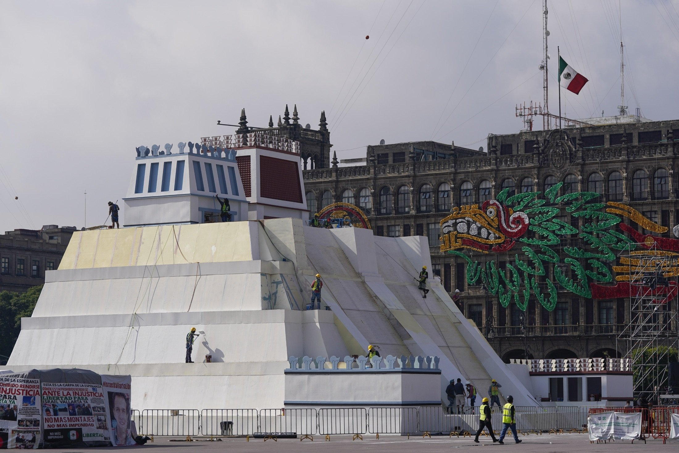 Workers build a replica of the Aztec Templo Mayor, with an image of the Pre-Columbian god Quetzalcoatl adorning the surrounding buildings, at Mexico City´s main square the Zocalo, Mexico, Aug. 9, 2021. (AP Photo)