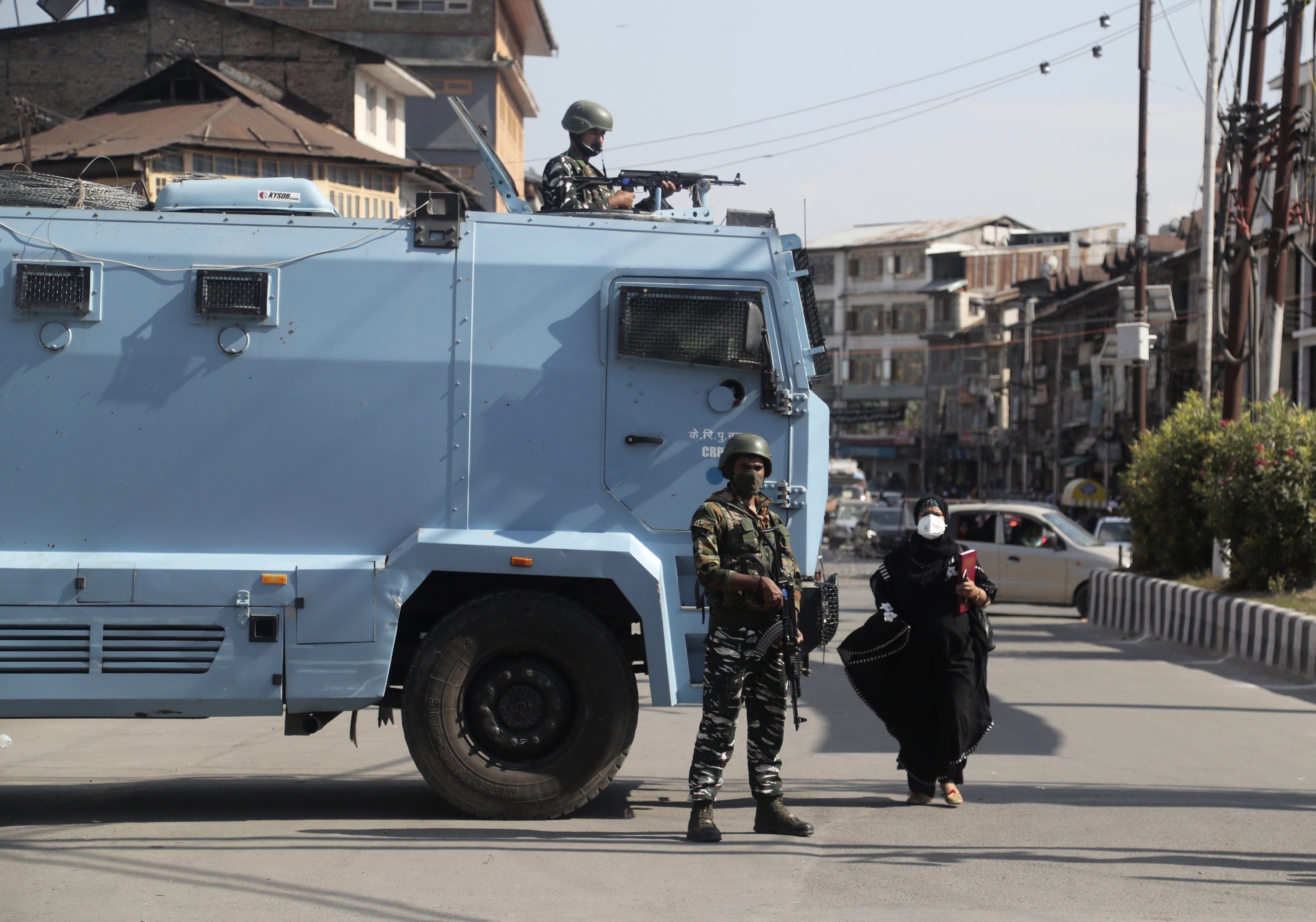 A Kashmiri woman walks past Indian paramilitary soldiers standing guard near the site of a grenade attack at a busy market in Srinagar, Indian controlled Kashmir, Tuesday, Aug. 10, 2021. (AP Photo)