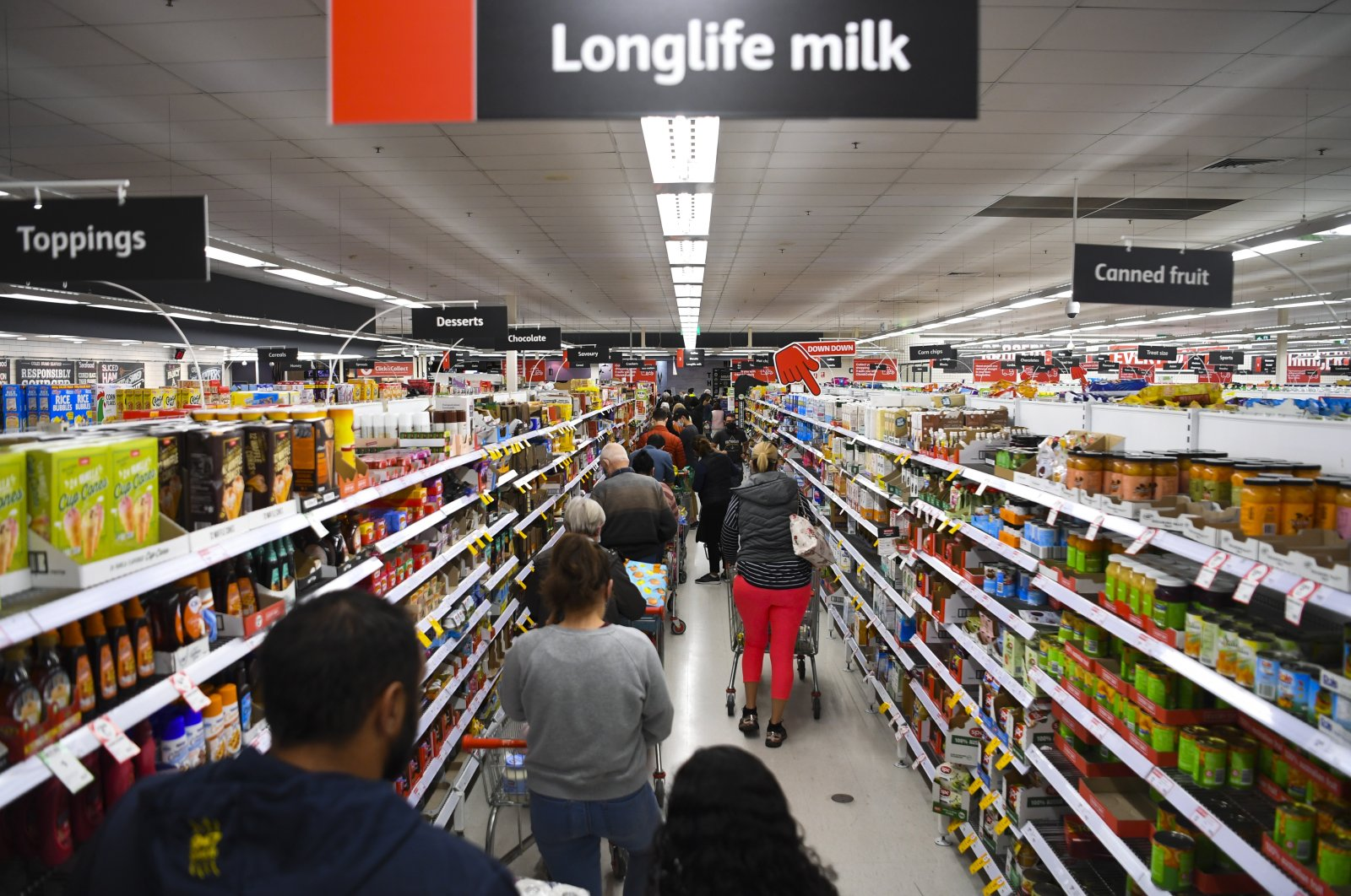 Customers stand in long lines at a check out counter at a Coles supermarket in the Woden area in Canberra, Australia, Aug. 12, 2021. (EPA Photo)
