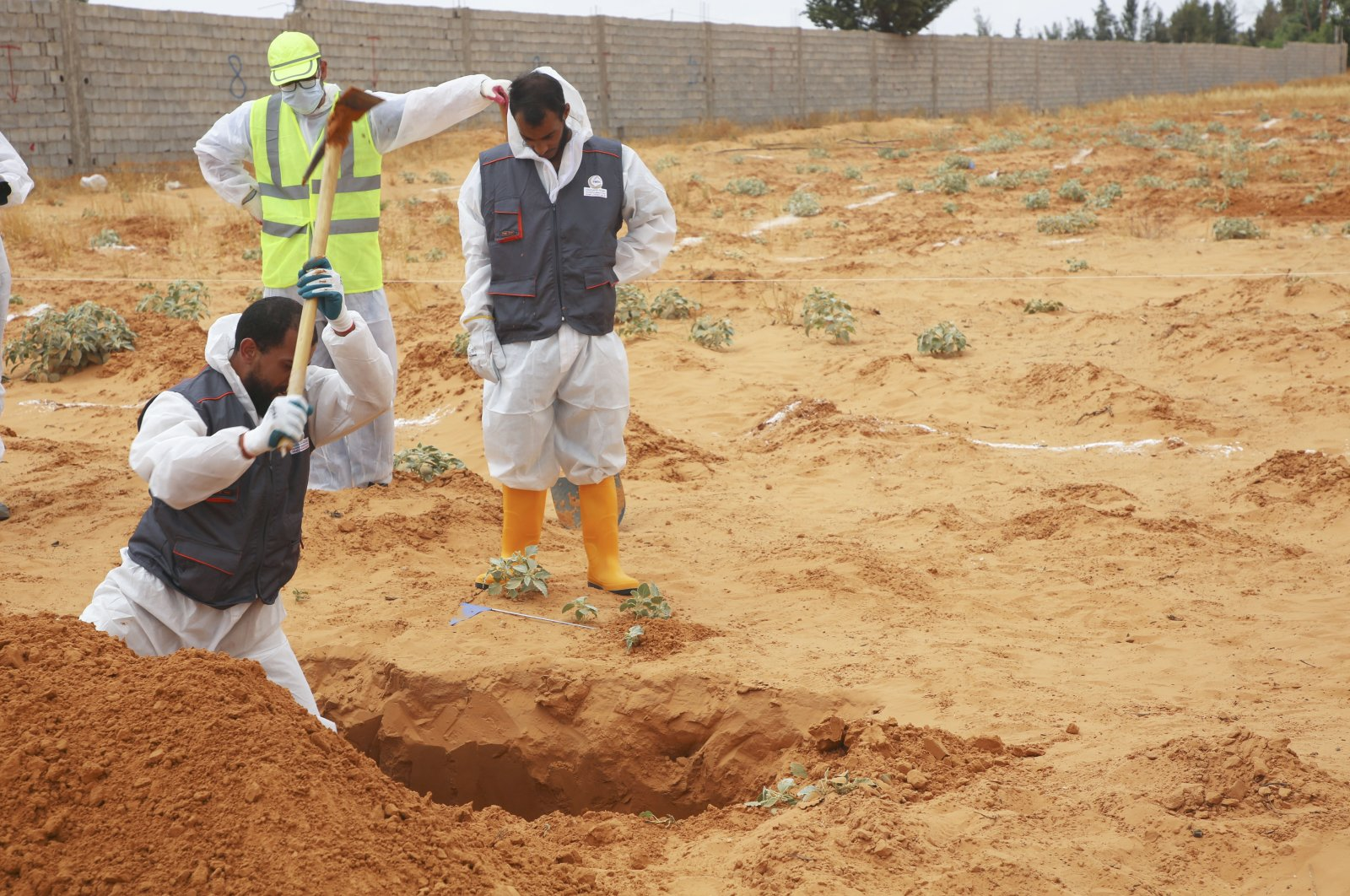 Libyan Ministry of Justice employees dig at the site of a suspected mass grave in the town of Tarhuna, Libya, June 23, 2020. (AP Photo)