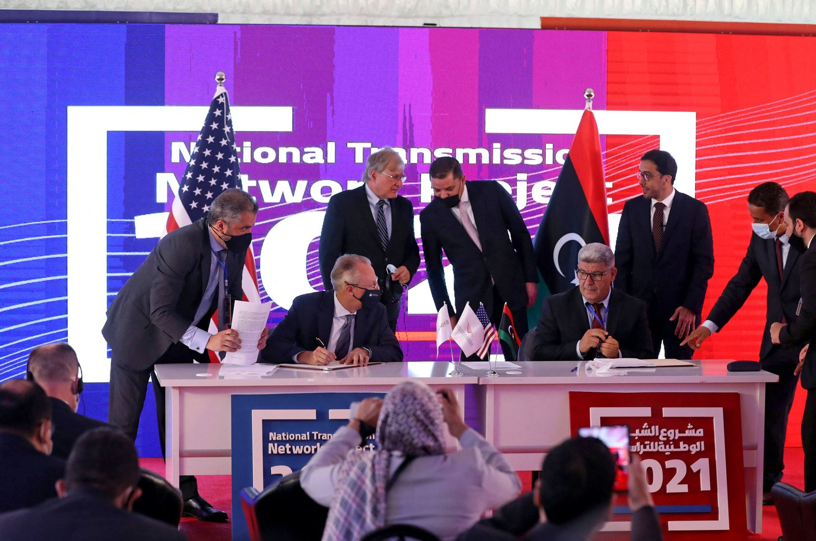 (Foreground L to R) Infinera's CEO and Director David Heard and Hatif Libya's Chairperson Muhammad Balras Ali sign a deal in the presence of (background L to R) U.S. Ambassador to Libya Richard Norland alongside Libyan Prime Minister Abdul Hamid Mohammed Dbeibah in Libya's capital Tripoli, July 26, 2021. (AFP Photo)