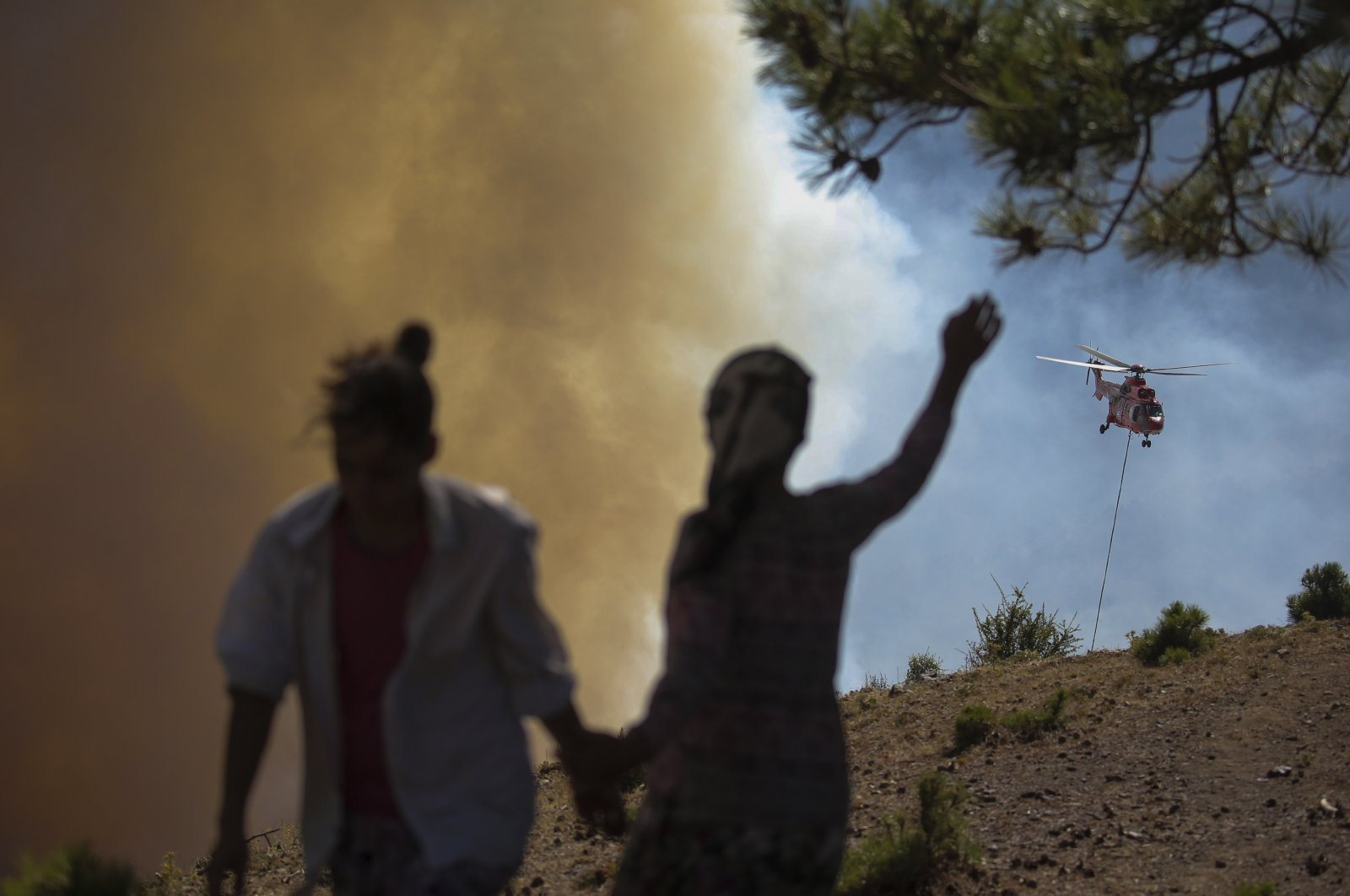 People watch as a helicopter participates in a wildfire extinguishing operation, in Köyceğiz, Muğla, southwestern Turkey on Aug. 9, 2021. (AP Photo)