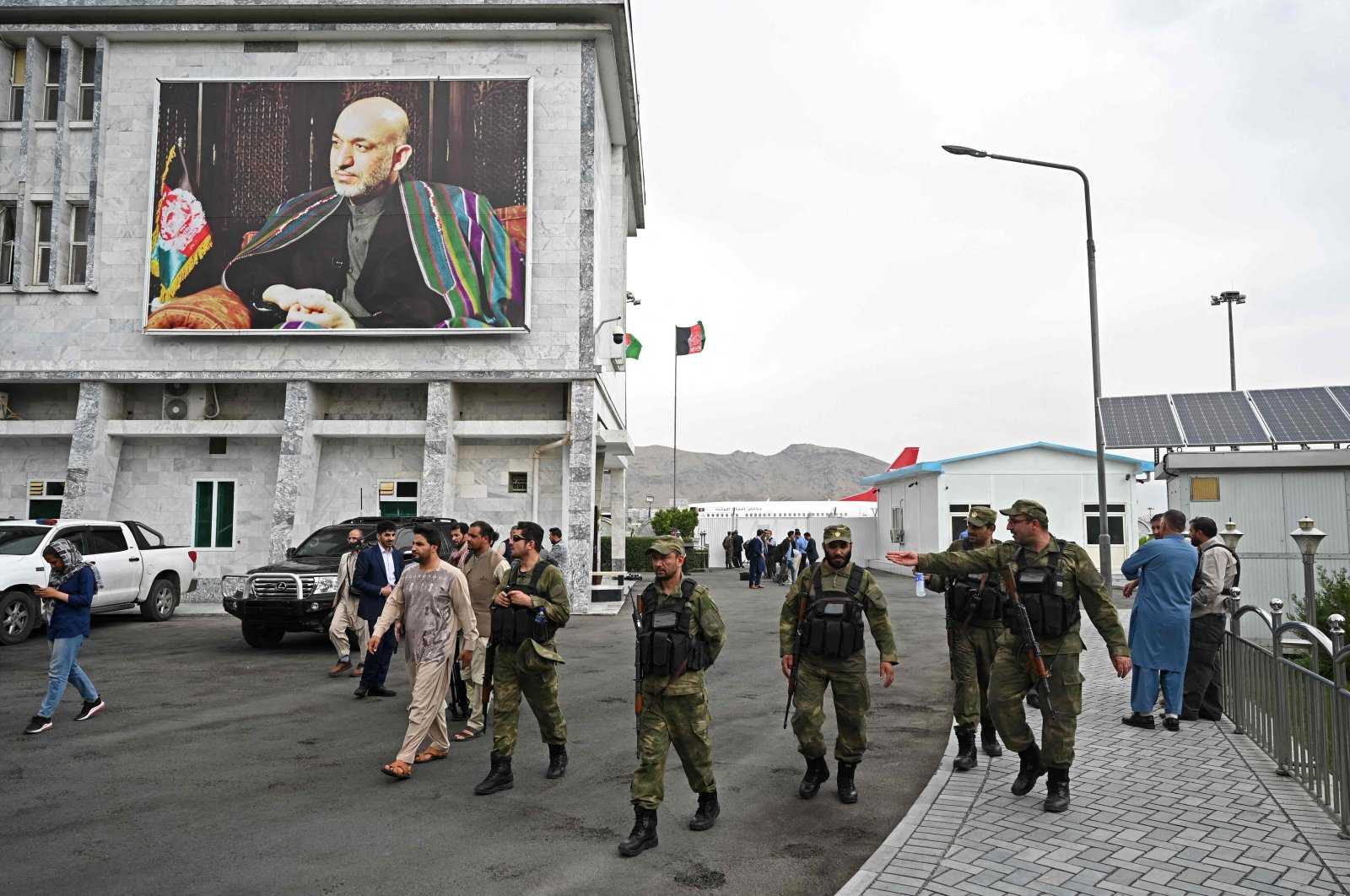 Security personnel walk past a poster of former Afghan President Hamid Karzai at the Hamid Karzai International Airport in Kabul on July 16, 2021. (AFP Photo)