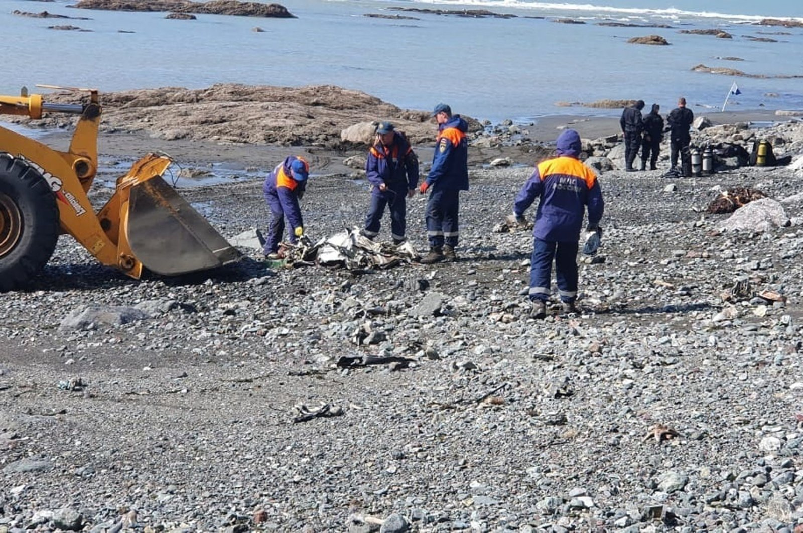 Emergency workers take part in the rescue operation at the spot where a Mi-8 helicopter crash-landed into Kuril Lake in the Kronotsky nature reserve on the Kamchatka peninsula, outside Petropavlovsk-Kamchatsky, Russia, Aug. 12, 2021. (Russian Emergency Situation Ministry via Reuters)