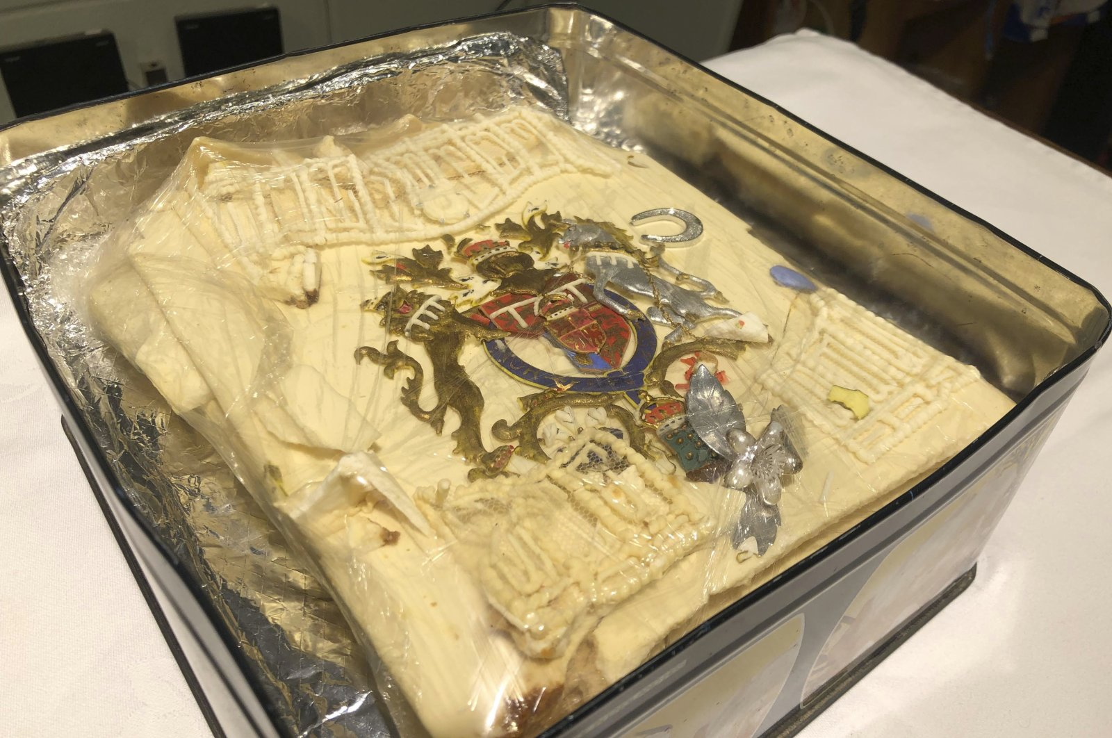 The tin containing the plastic-wrapped slice of cake from one of the 23 official wedding cakes made for the Royal Wedding of Prince Charles and Lady Diana Spencer, Dominic Winter Auctioneers in Cirencester, England, Aug. 11, 2021. (Claire Hayhurst/PA via AP)