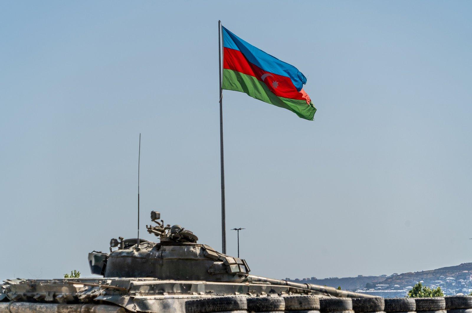 Azerbaijan flag flying above a captured Armenian tank in Trophy Park, Baku, Azerbaijan, June 16, 2021 (Getty Images)