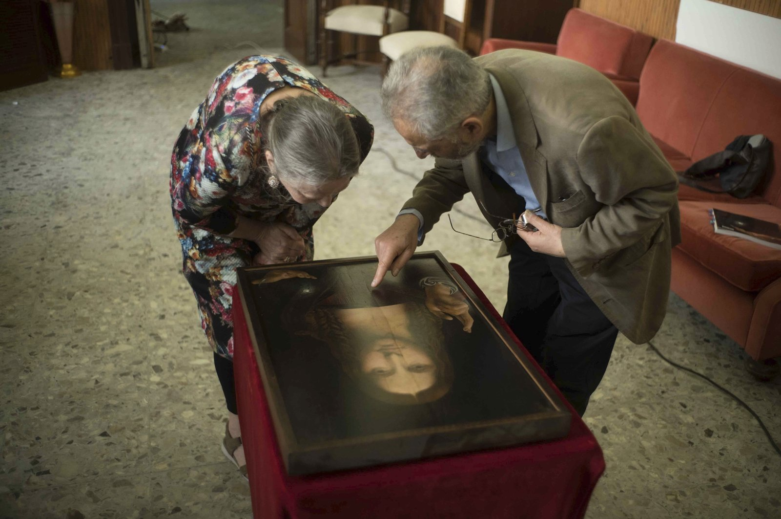 """Dianne Modestini (L), and Ashok Roy inspectthe Naples copy of the Salvator Mundi in a scene from the documentary """"The Lost Leonardo."""" (Sony Pictures Classics via AP)"""