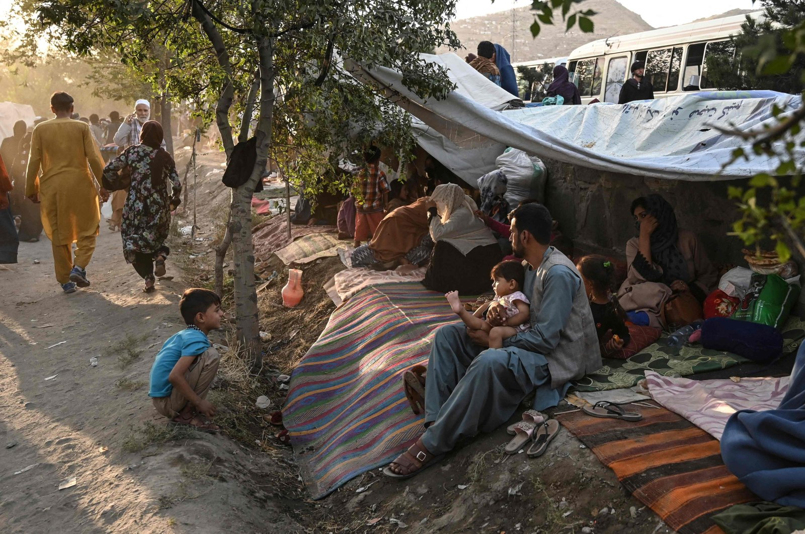 Internally displaced Afghan families, who fled from Kunduz, Takhar and Baghlan province due to battles between Taliban and Afghan security forces, sit in front of their temporary tents at Sara-e-Shamali in Kabul, Afghanistan on Aug. 11, 2021. (AFP Photo)