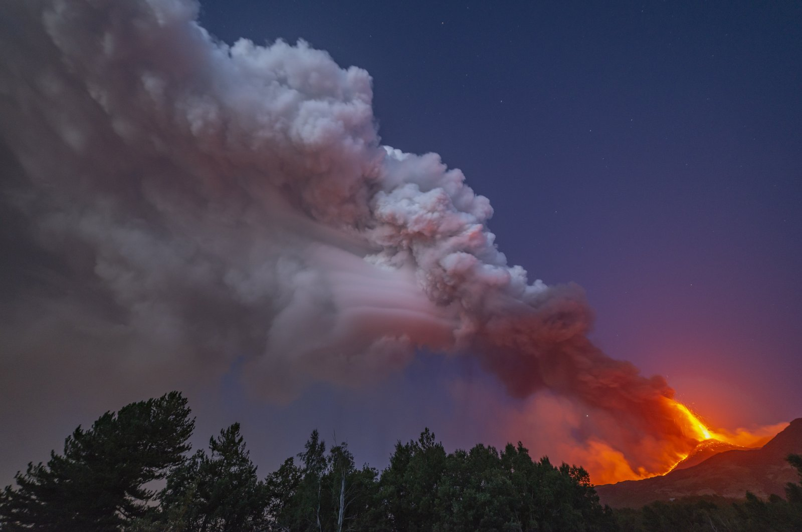Smoke billows from the Mount Etna volcano as seen from Linguaglossa, Sicily, Aug. 9, 2021. (AP Photo)