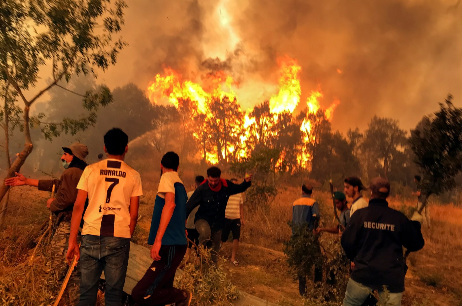 Villagers attempt to put out a wildfire in Achallam village, in the mountainous Kabylie region of Tizi Ouzou, east of Algiers, Algeria, Aug. 11, 2021. (Reuters Photo)