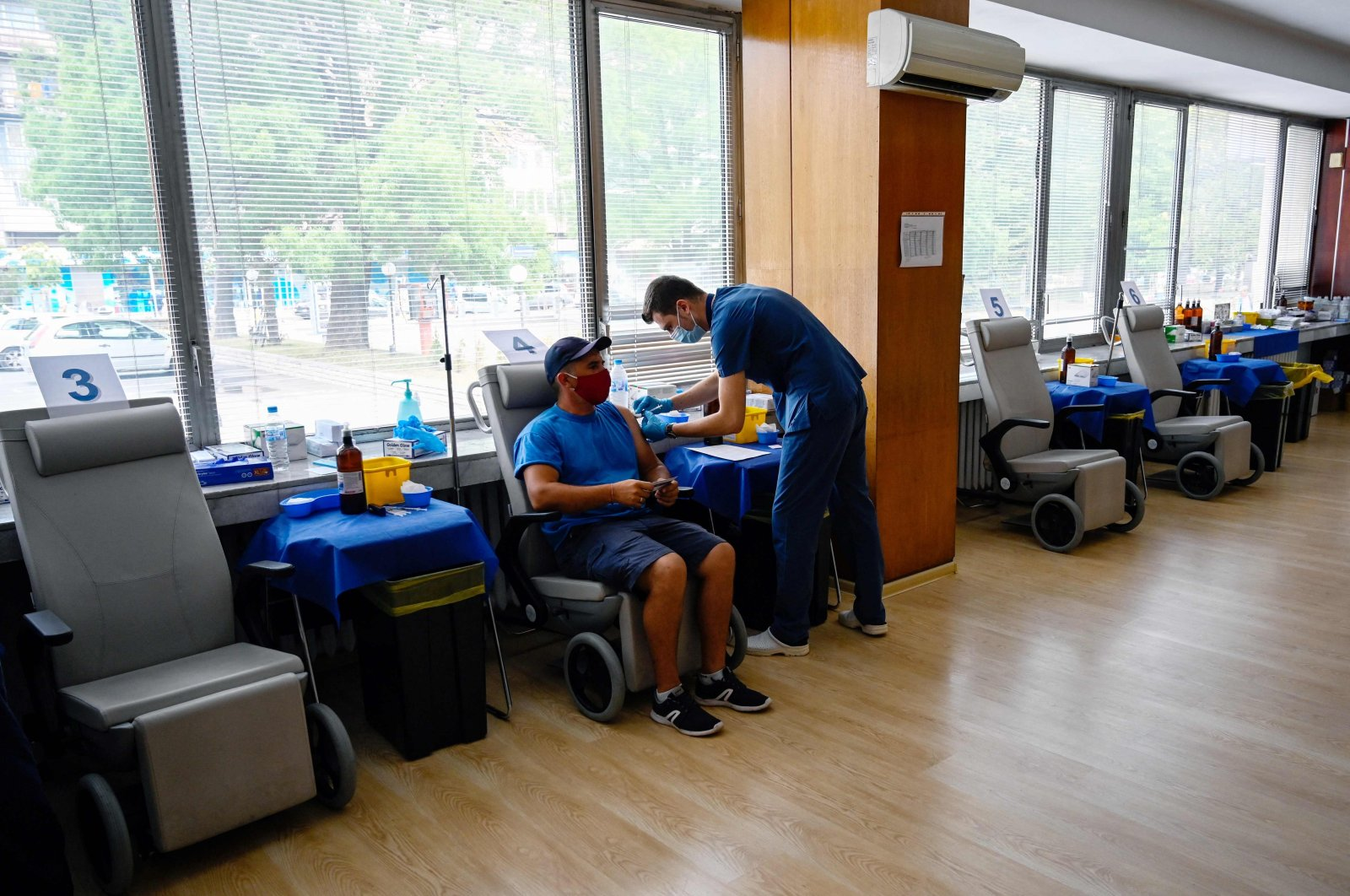 This photograph taken on August 6, 2021, shows a healthcare worker vaccinating a patient at a COVID-19 vaccination centre at The Military Medical Academy in Sofia, where a variety of vaccines are available: AstraZeneca, Pfizer Biotech, Moderns and Jansen. (AFP Photo)