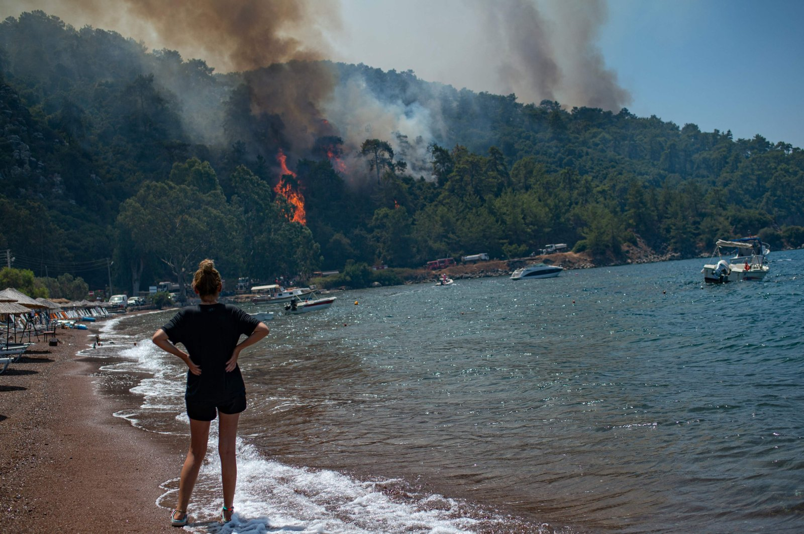 A woman watches the forest burning from a beach in Muğla, Turkey, on Aug. 3, 2021. (AFP Photo)