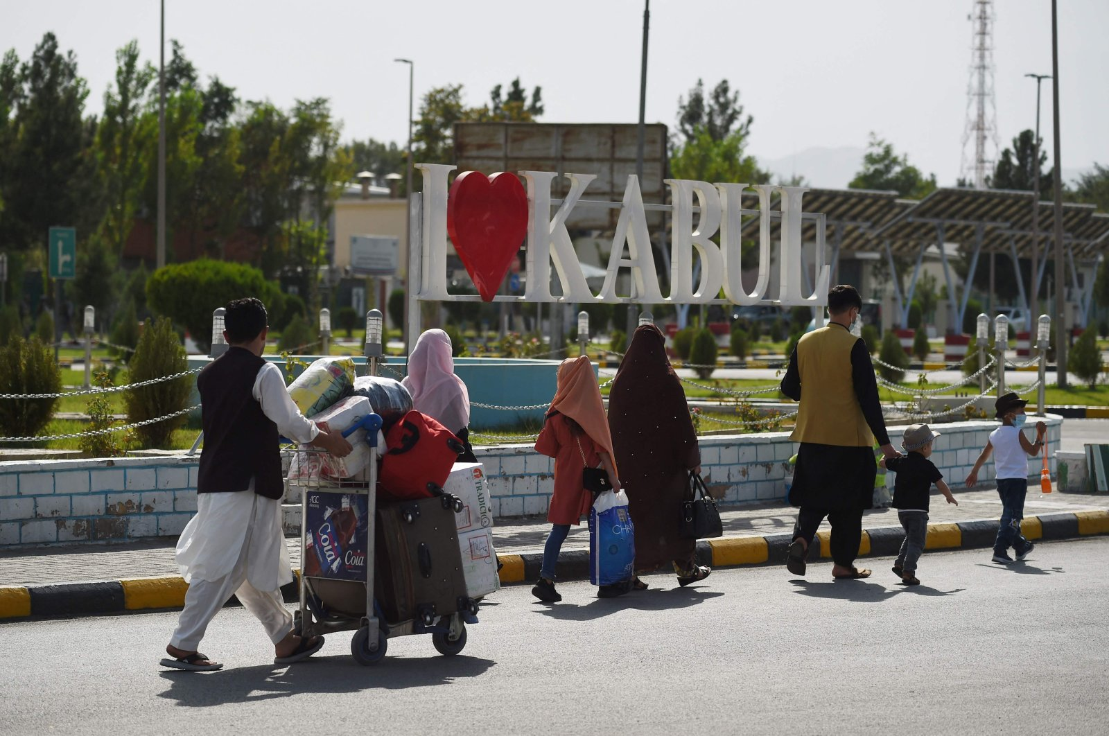 Afghan passengers carry their belongings as they exit the domestic terminal, at Kabul Hamid Karzai International Airport, Afghanistan, Aug. 8, 2021. (AFP Photo)