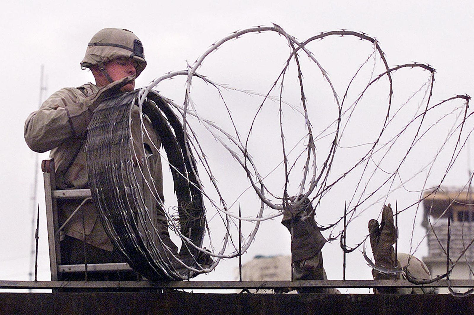 In this file photo, a U.S. Marine installs barbed wire to secure the walls of the U.S. Embassy in Kabul, Afghanistan, Jan. 11, 2002. (AFP File Photo)