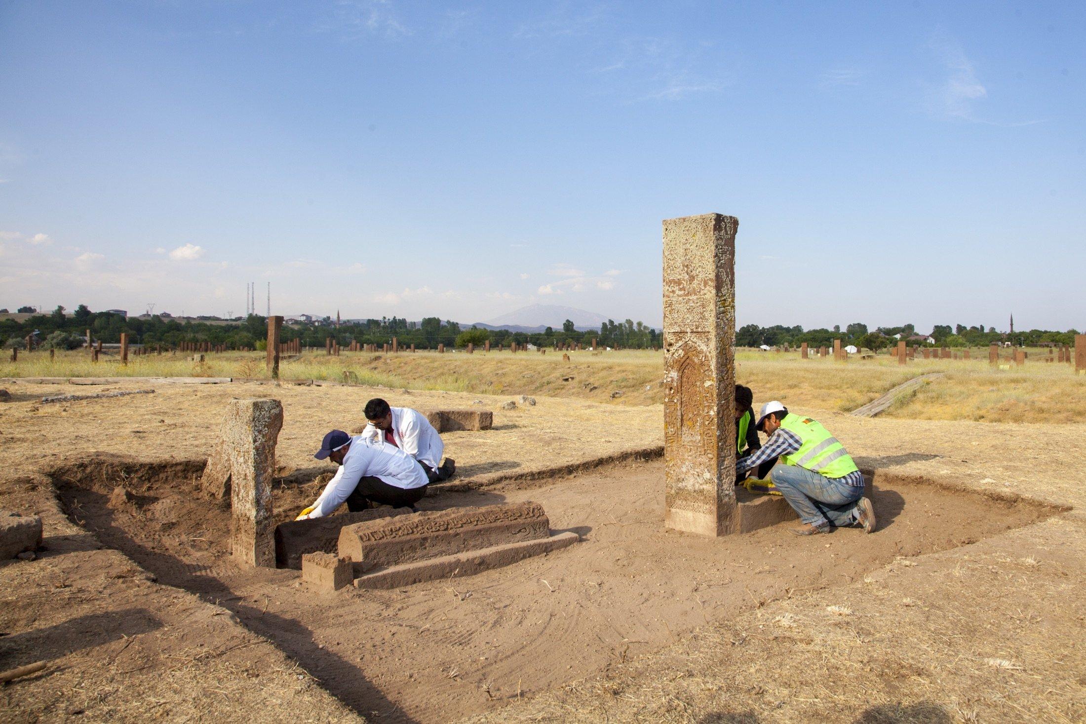 Kazı ekibi üyeleri, 13 Ağustos 2021'de Türkiye'nin Beatles ilçesindeki kimliği belirsiz Selçuklu mezarlarının bir tür geleneksel anıt mezarı olan Sandukas üzerinde arkeolojik çalışma yürütüyor.  (AA fotoğrafı)