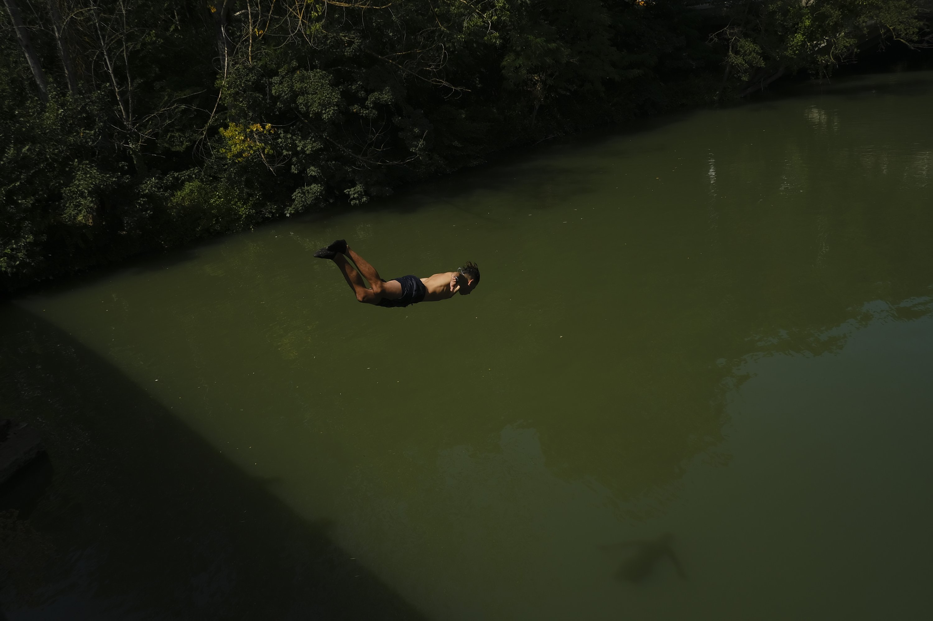 A teenager dives into water to cool off in the Arga River during a heatwave in Pamplona, northern Spain, Aug. 13, 2021. (AP Photo)