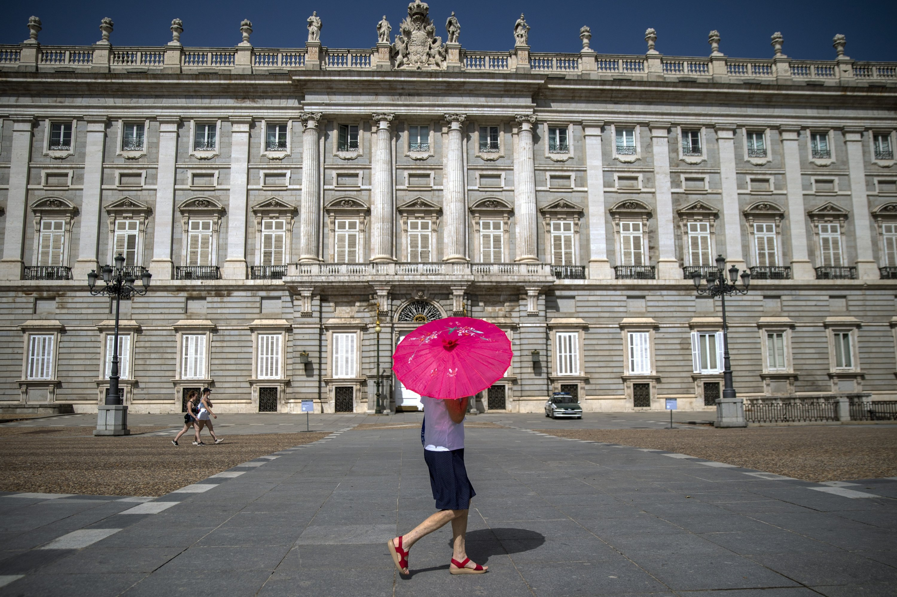 A woman with an umbrella walks past the Royal Palace during a heatwave in Madrid, Spain, Aug. 13, 2021. (AP Photo)