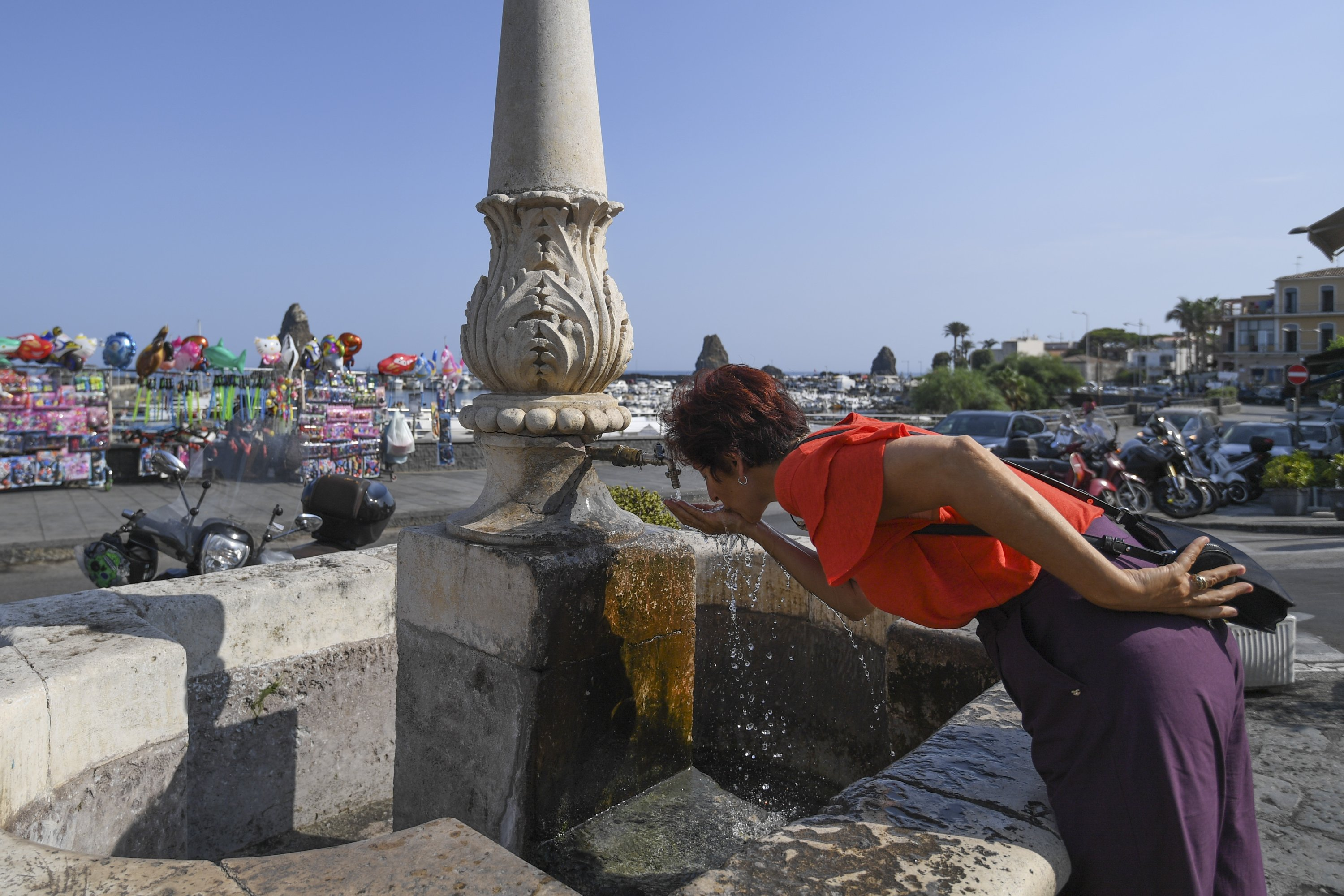 A woman refreshes herself at a fountain in Aci Trezza, near Catania, Sicily, Italy, Aug. 13, 2021. (AP Photo)