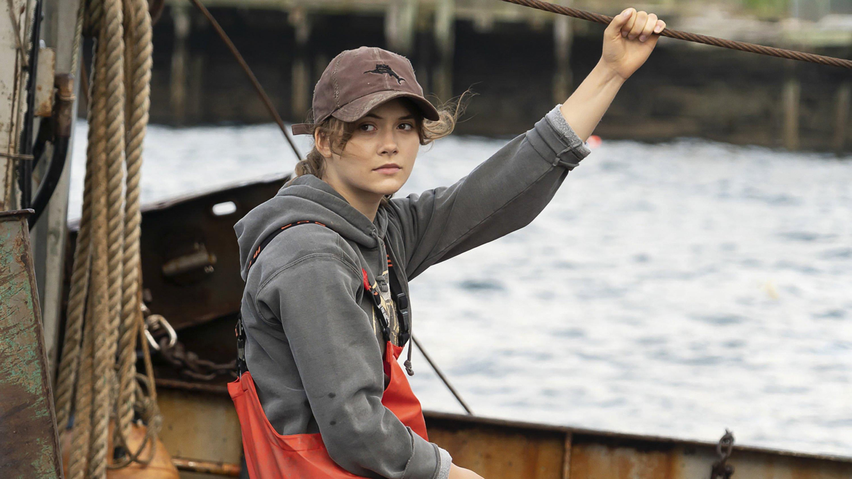 "Emilia Jones stands on a boat, in a scene from the film ""CODA."" (Apple TV+ via AP)"