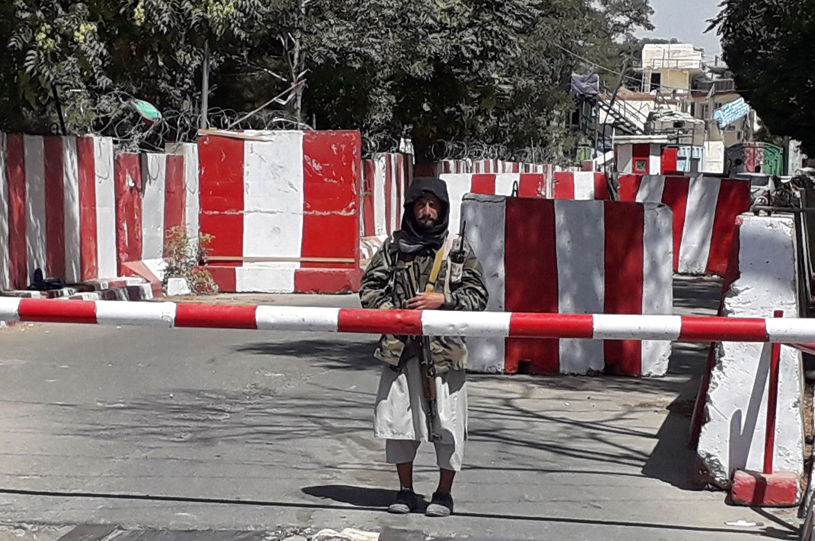 A Taliban fighter stands guard at the entrance of the police headquarters in Ghazni, Afghanistan, Aug. 12, 2021. (AFP Photo)