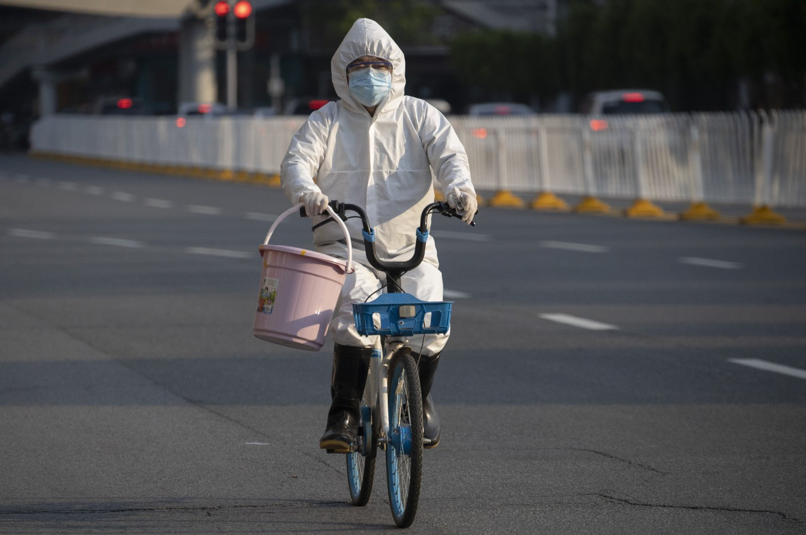 A resident wearing mask and suit against the coronavirus cycles in Wuhan, Hubei province, central China, April 12, 2020. (AP Photo)
