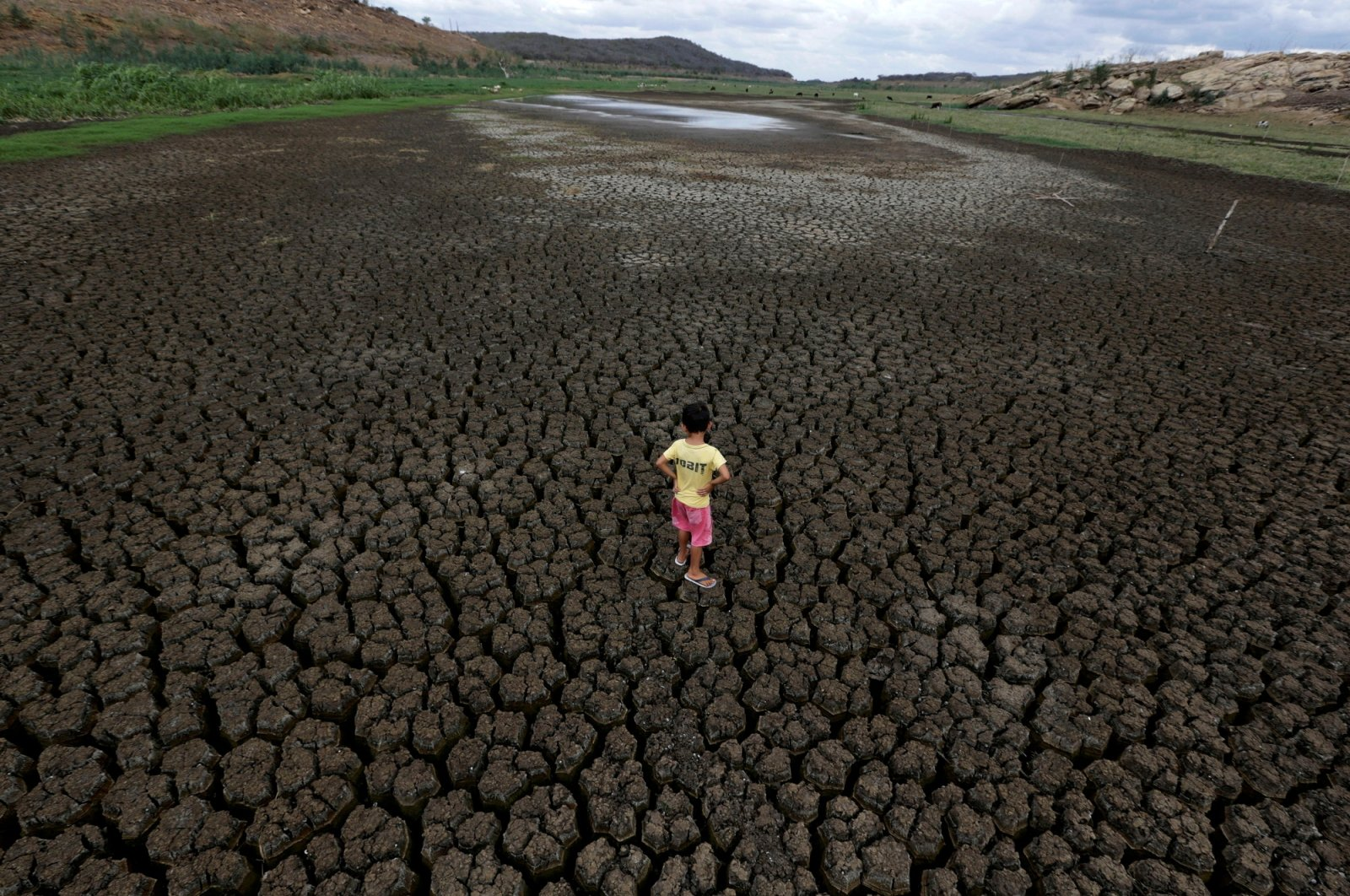 A boy stands on the cracked ground of the Boqueirao reservoir in the Metropolitan Region of Campina Grande, Paraiba state, Brazil, Feb. 13, 2017. (Reuters Photo)