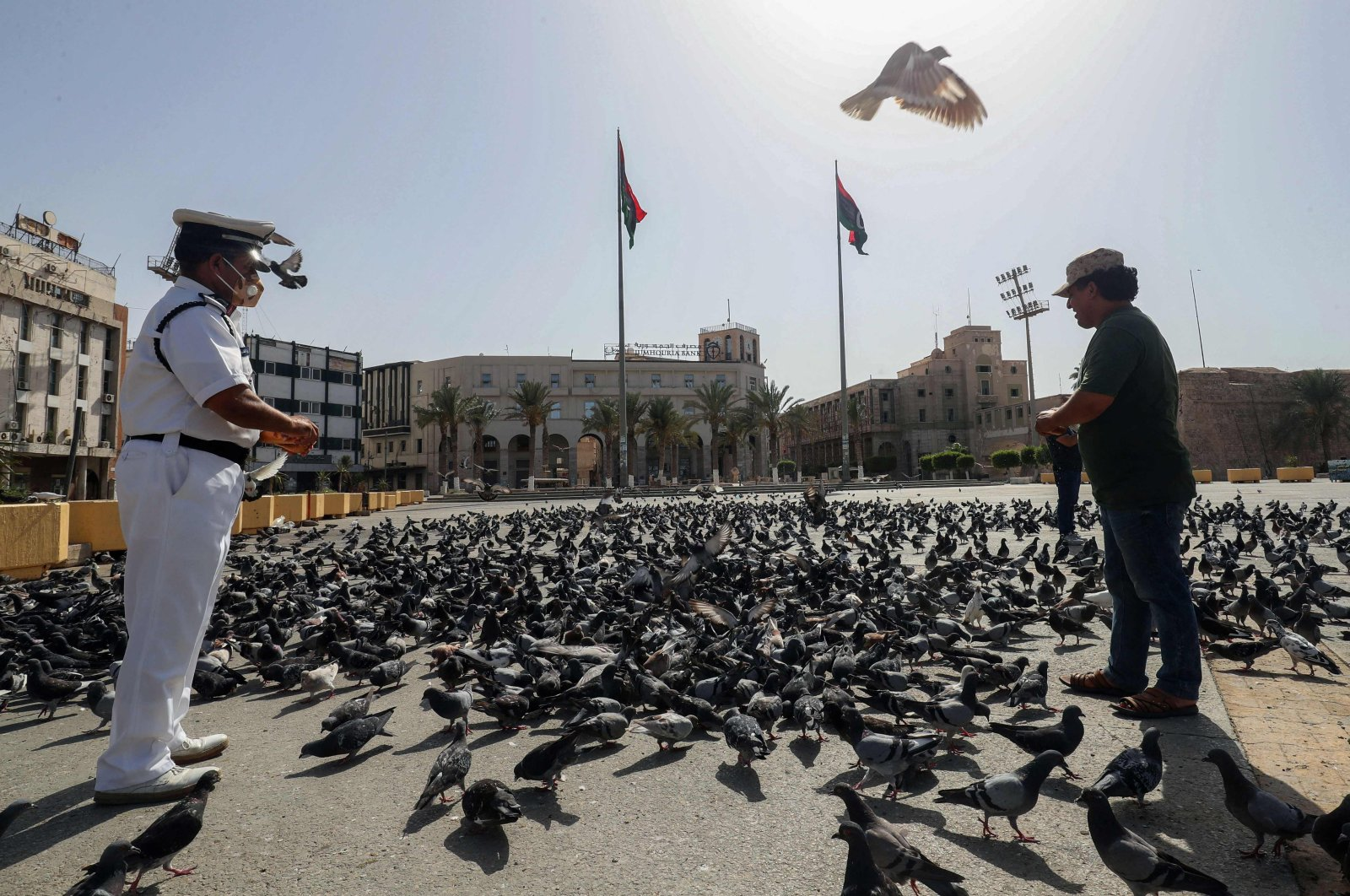 Men feed pigeons in an empty Martyrs square in downtown Tripoli, a day after authorities announced a total curfew through the weekend to mitigate the spread of COVID-19, Tripoli, Libya, August, 7, 2021. (Photo by Mahmud TURKIA / AFP)