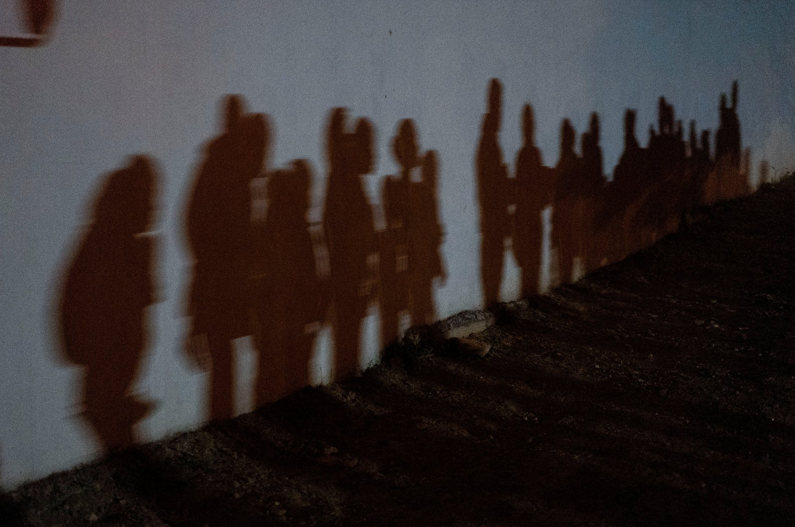 Asylum-seeking migrant families cast shadows on a wall as they form a queue to be processed by the U.S. Border Patrol after crossing the Rio Grande river into the United States from Mexico in Roma, Texas, U.S., Aug. 12, 2021. (Reuters Photo)