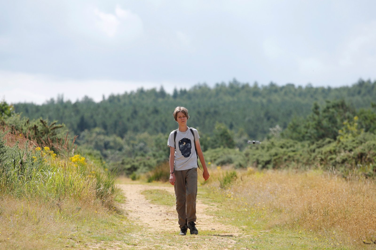 """Jude Walker, 11, during his 210-mile (340-km) walk from Yorkshire to London over 21 days to raise awareness for """"the zero carbon campaign"""" petition, which calls for the government to implement a carbon tax, in Milton Keynes, Britain, Aug. 10, 2021. (REUTERS/Andrew Couldridge)"""