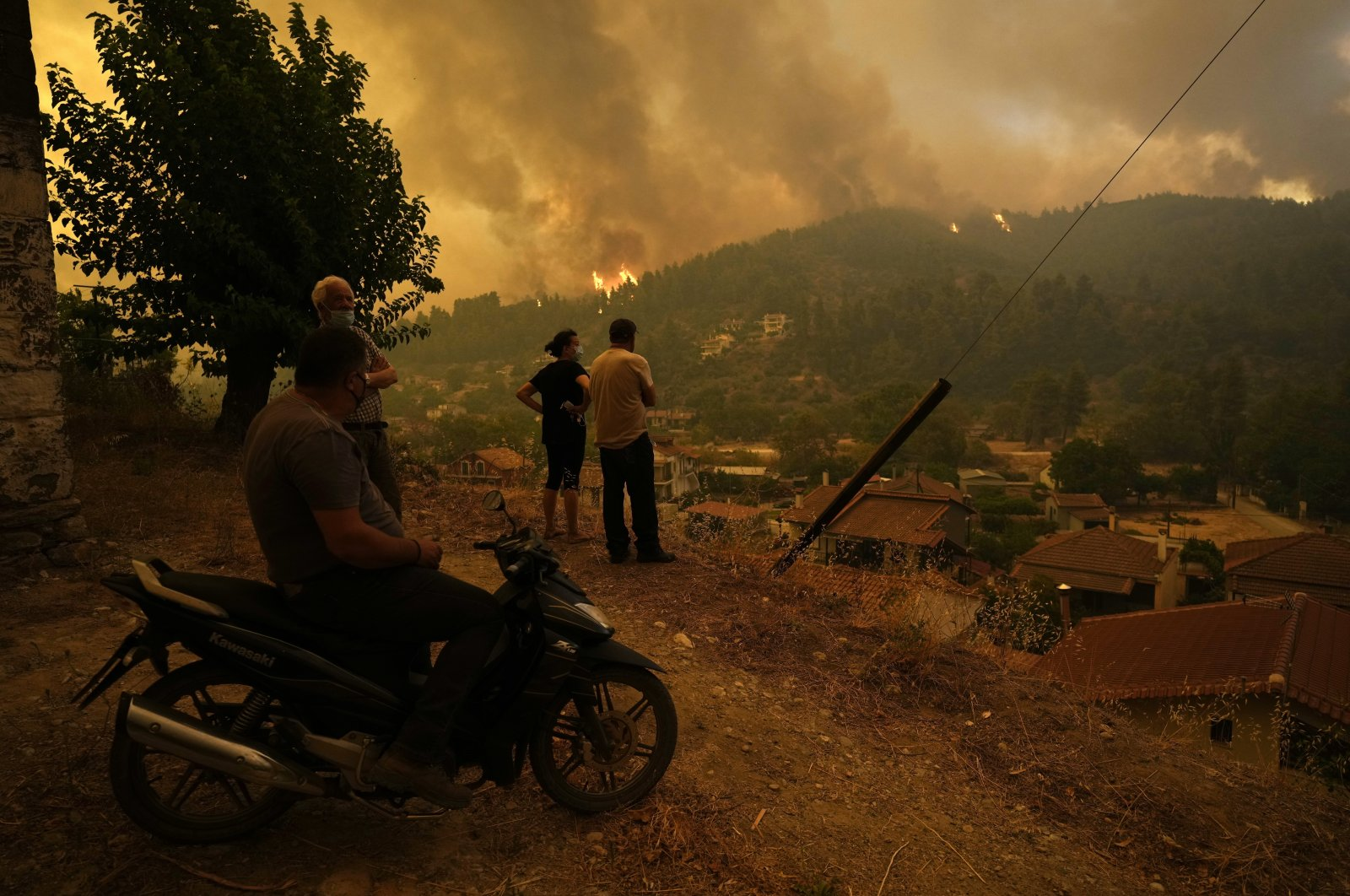 Local residents stand on a hill as flames approaching at Gouves village on the island of Evia, about 185 kilometers (115 miles) north of Athens, Greece, Aug. 8, 2021. (AP Photo)