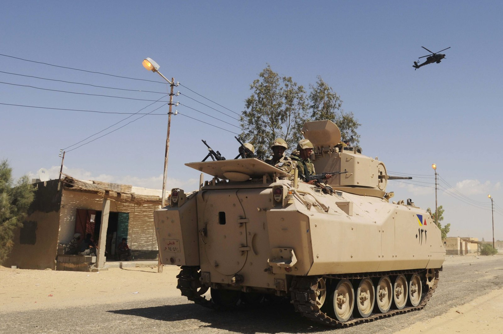 Egyptian Army soldiers patrol in an armored vehicle backed by a helicopter gunship during a sweep through villages in Sheikh Zuweyid, north Sinai, Egypt, May 12, 2013. (AP Photo)