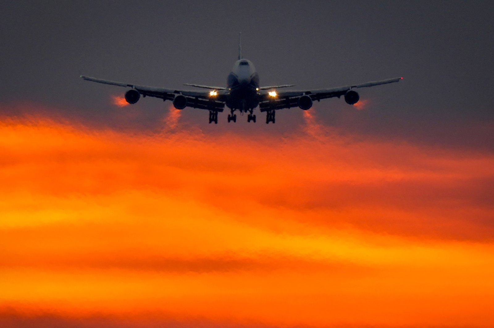 An aircraft approaches the international airport in Frankfurt as the sun rises, Germany, Aug. 9, 2021. (AP Photo)