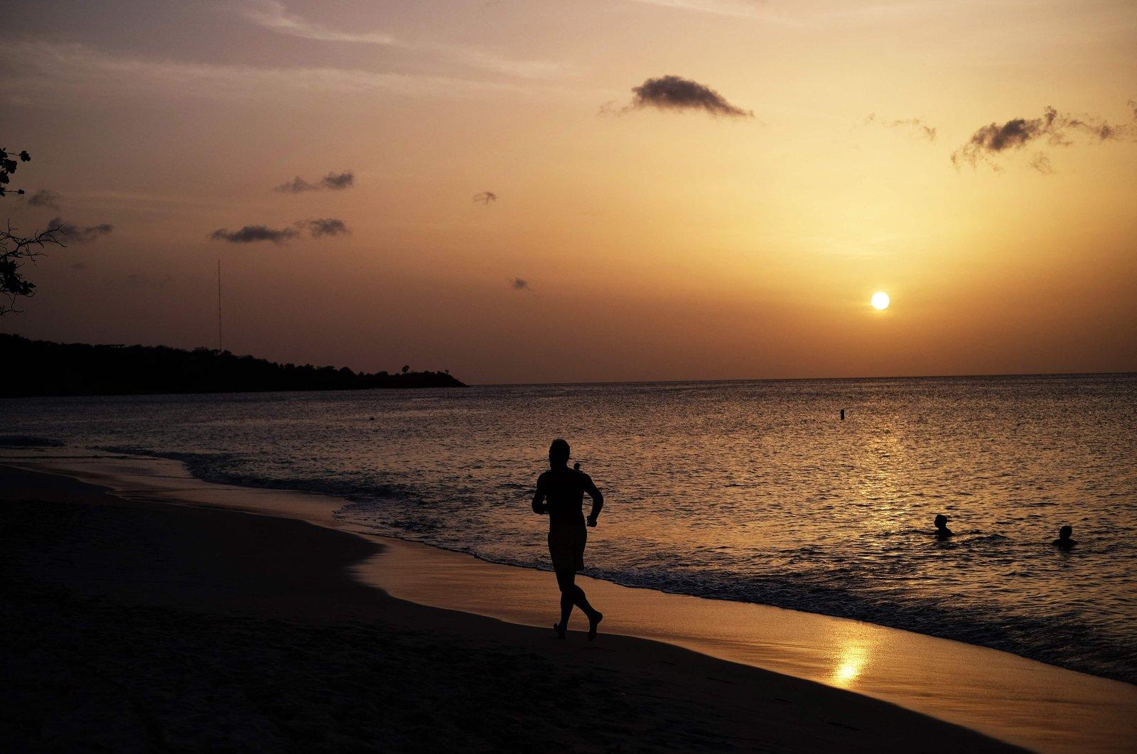 A man jogs along a beach in Saint George's, Grenada, on April 20, 2015. (AFP Photo)