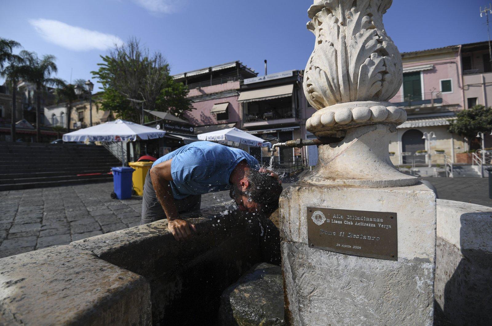 A man refreshes himself at a fountain in Aci Trezza, near Catania, Sicily, Italy, Aug. 13, 2021. (AP Photo)