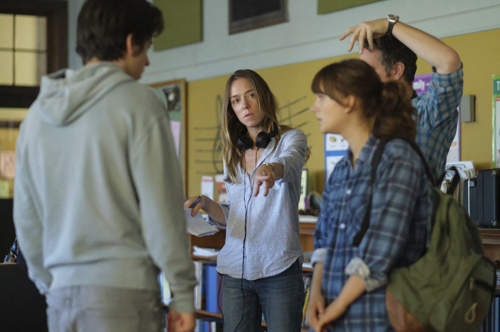 "DirectorSian Heder (C) talks with actorsEmilia Jones (R), and Ferdia Walsh-Peelo, on the set of the film ""CODA.""(Apple TV+ via AP)"