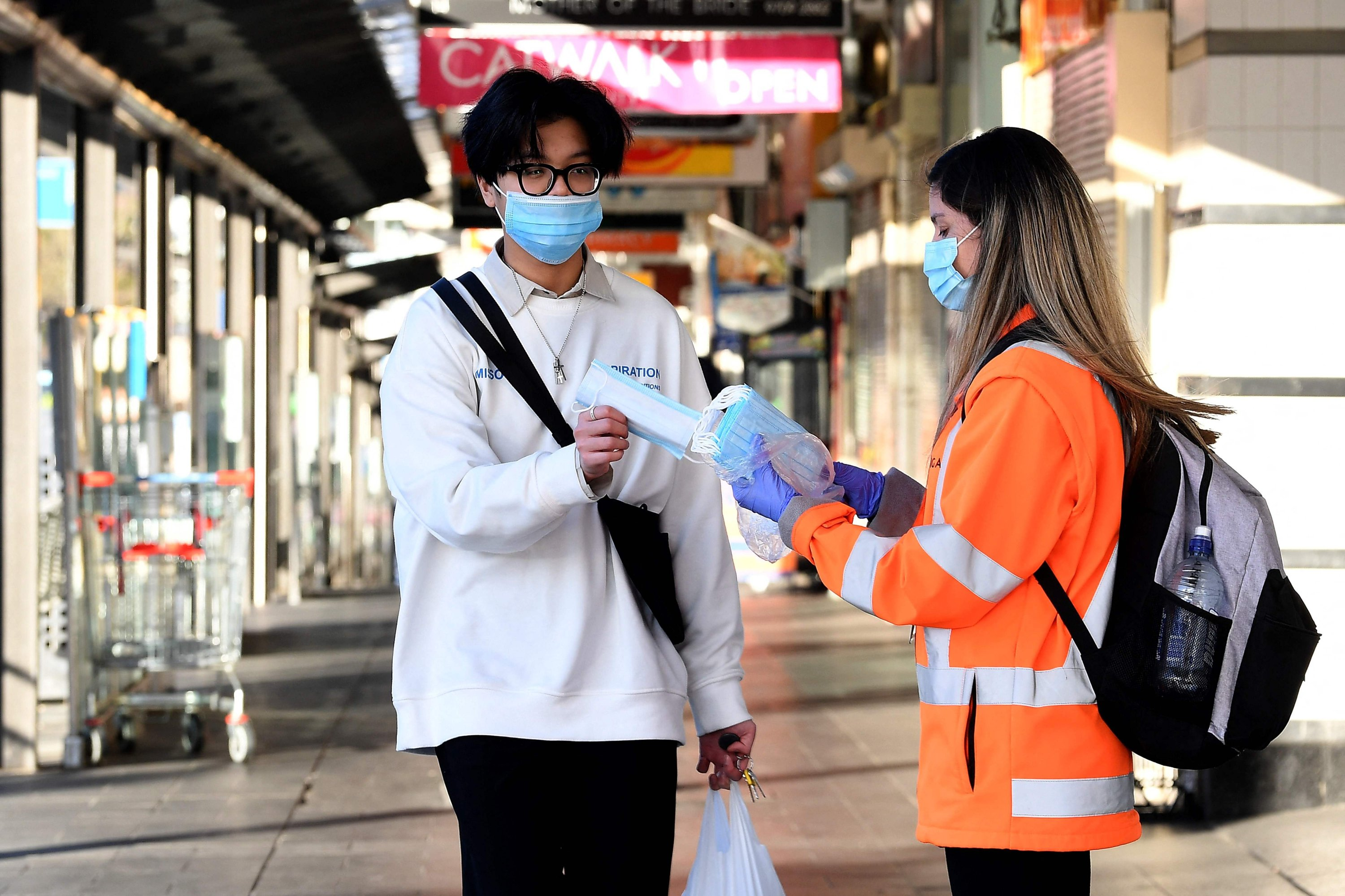 A volunteer distributes face masks in Bankstown suburb of Sydney as the city's more than five million people are enduring their seventh week under stay-at-home orders, Sydney, Australia, Aug. 11, 2021. (AFP Photo)