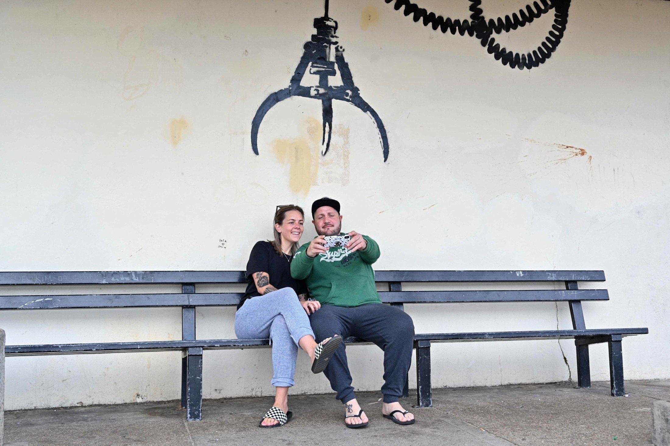 A couple take a selfie photograph below a graffiti artwork of an amusement arcade grabber, which bears the hallmarks of street artist Banksy, on a wall in Gorleston-on-Sea, U.K., Aug. 8, 2021. (AFP Photo)