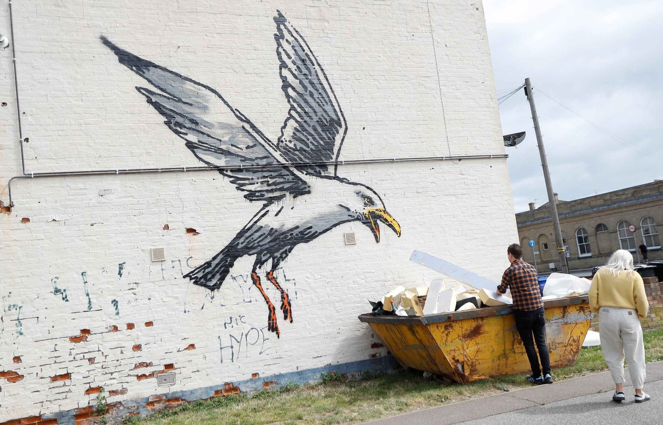 A man interacts with artwork created by Banksy in Lowestoft, U.K., Aug. 8, 2021. (Reuters Photo)