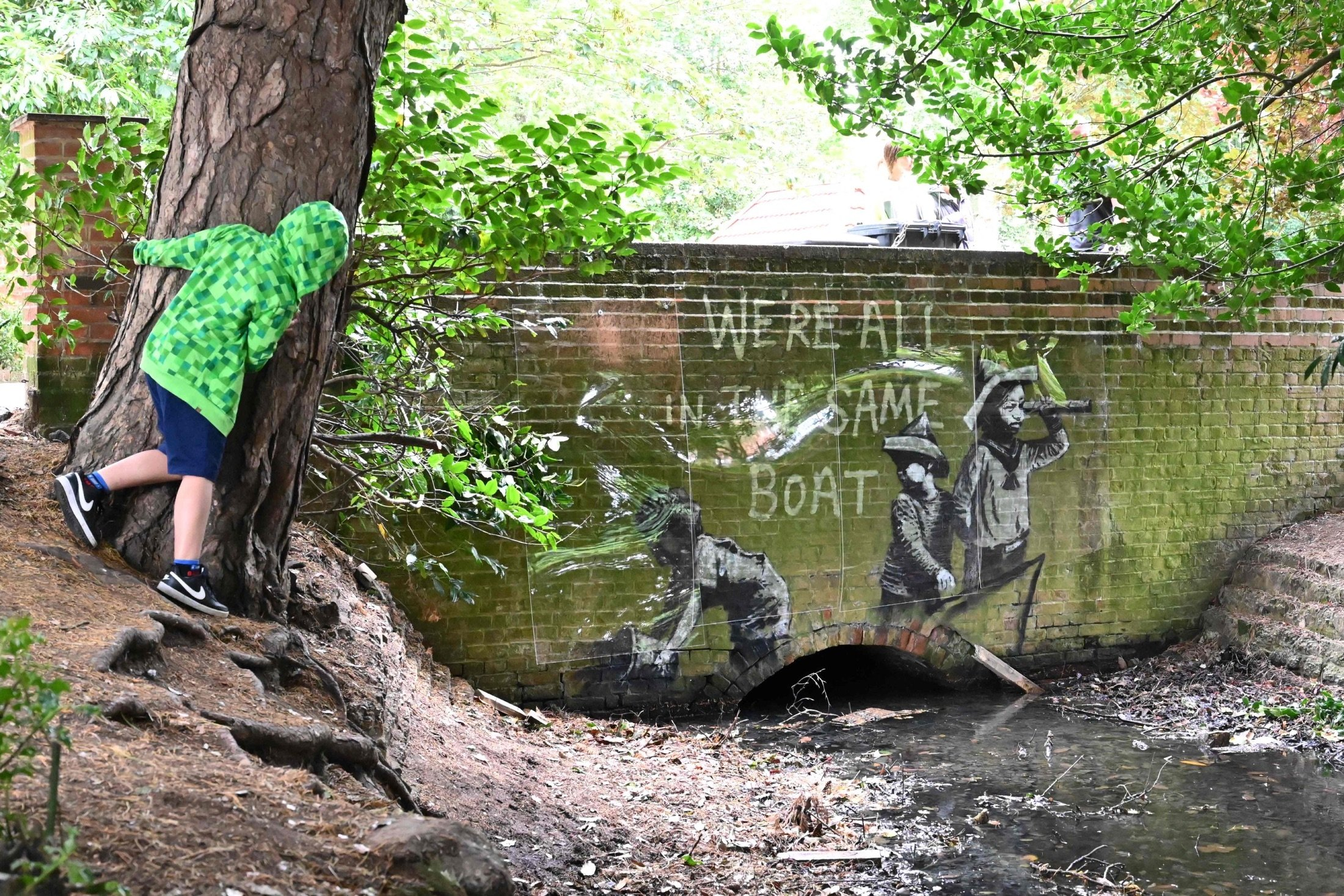 A stensil of children playing at being sailors is the subject of a graffiti artwork bearing the hallmarks of street artist Banksy can be seen on the wall of a bridge in Everitt Park in Lowestoft, U.K., Aug. 8, 2021. (AFP Photo)