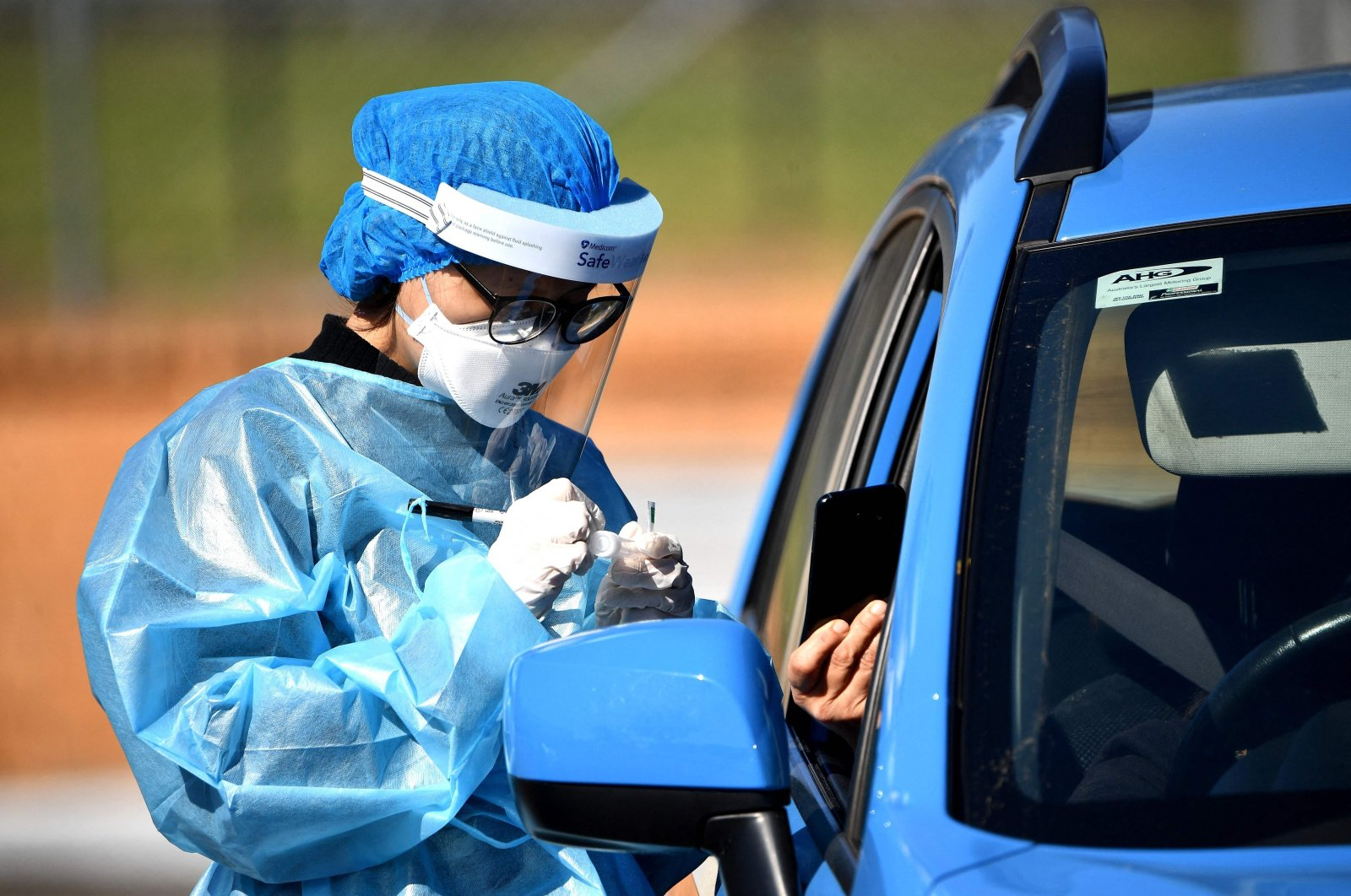A health worker takes a swab sample at a COVID-19 drive through testing site in the Smithfield suburb of Sydney, Australia, Aug. 12, 2021. (AFP Photo)