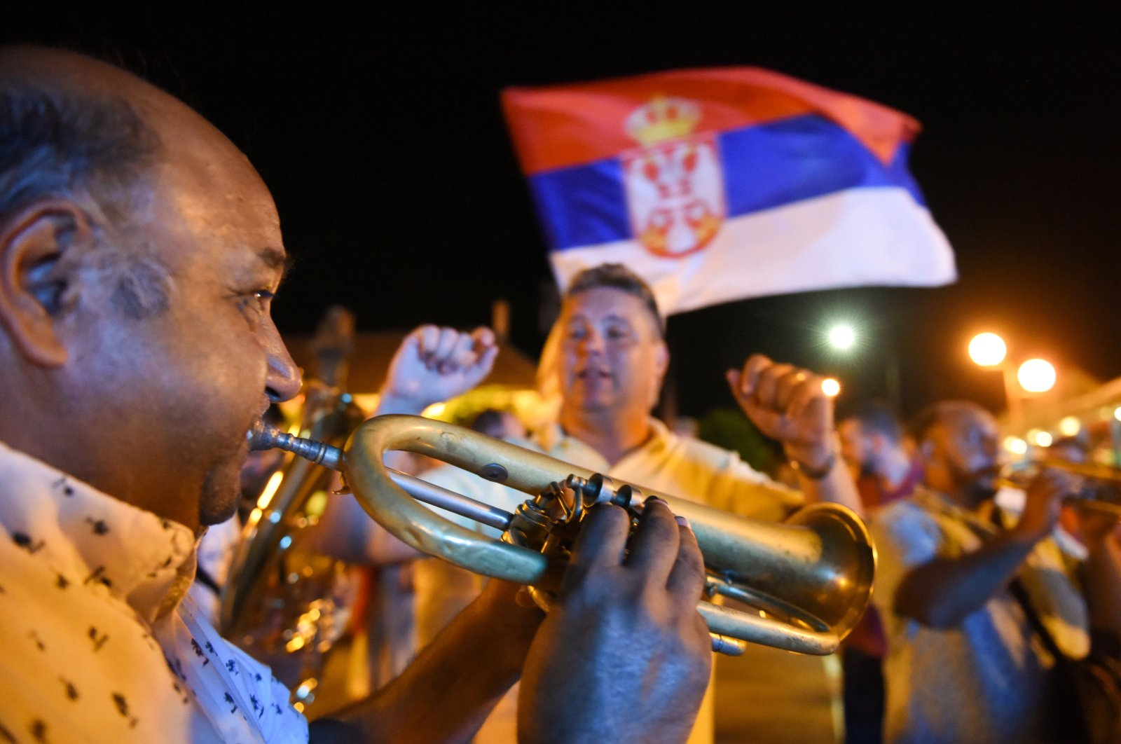 People sing and dance on a street during the annual brass band festival, in Guca, Serbia, Aug. 13, 2021. (Reuters Photo)